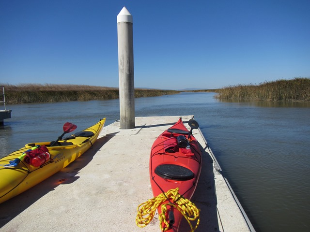 Two kayaks on floating dock, with water and marshlands beyond