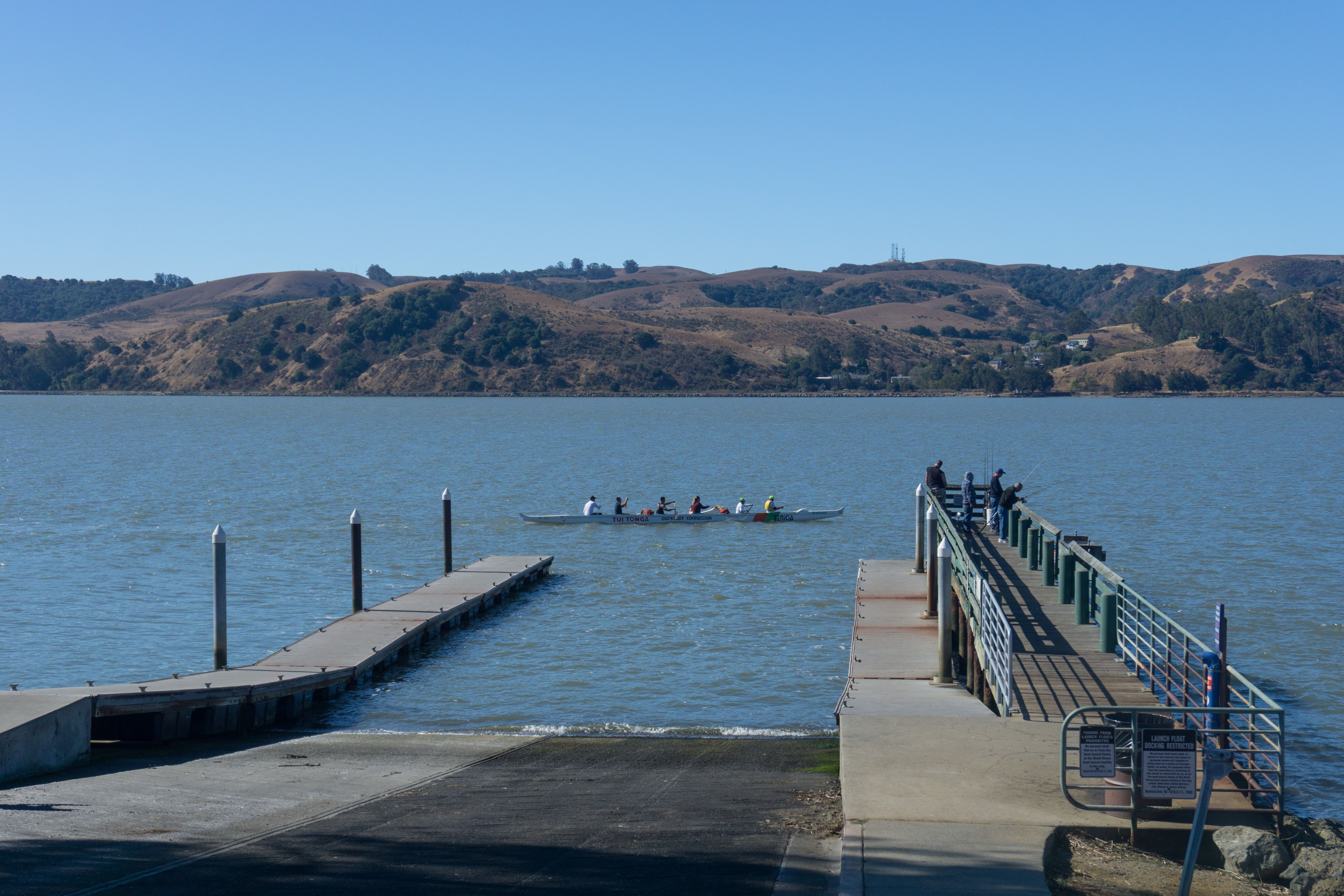 Boat ramp descending to water. Rowers in long sculling shell pass by
