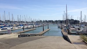 Boat ramp descends into water, with many boats moored at docks offshore