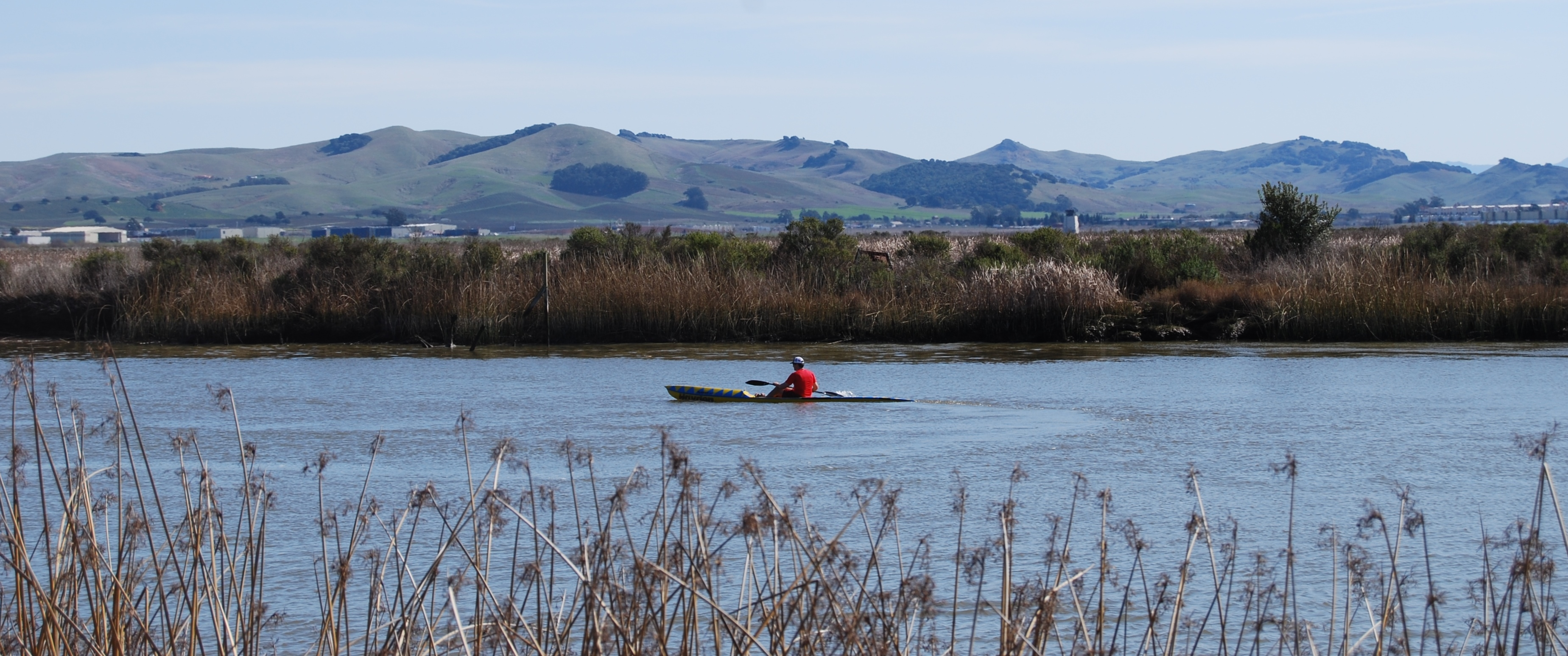 Lone paddler looking toward marsh and hills in distance