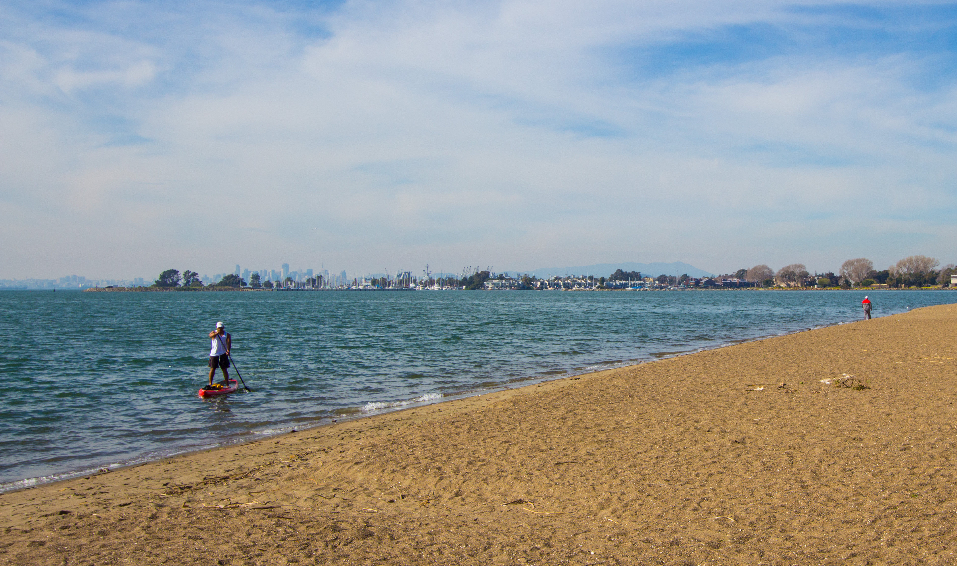 wide sandy beach, with a lone standup paddler just offshore