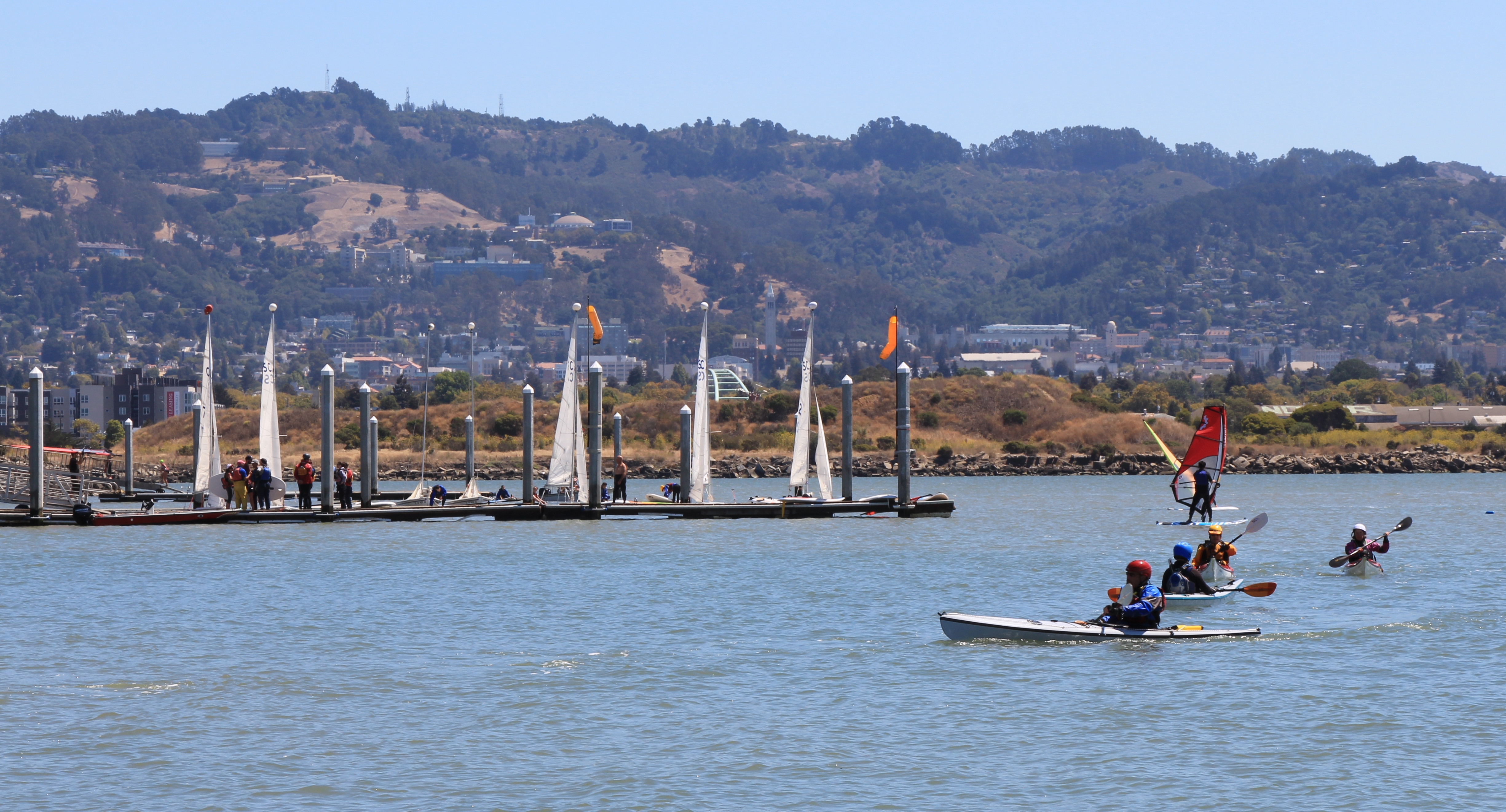 kayakers paddling in front of marina, with hills beyond
