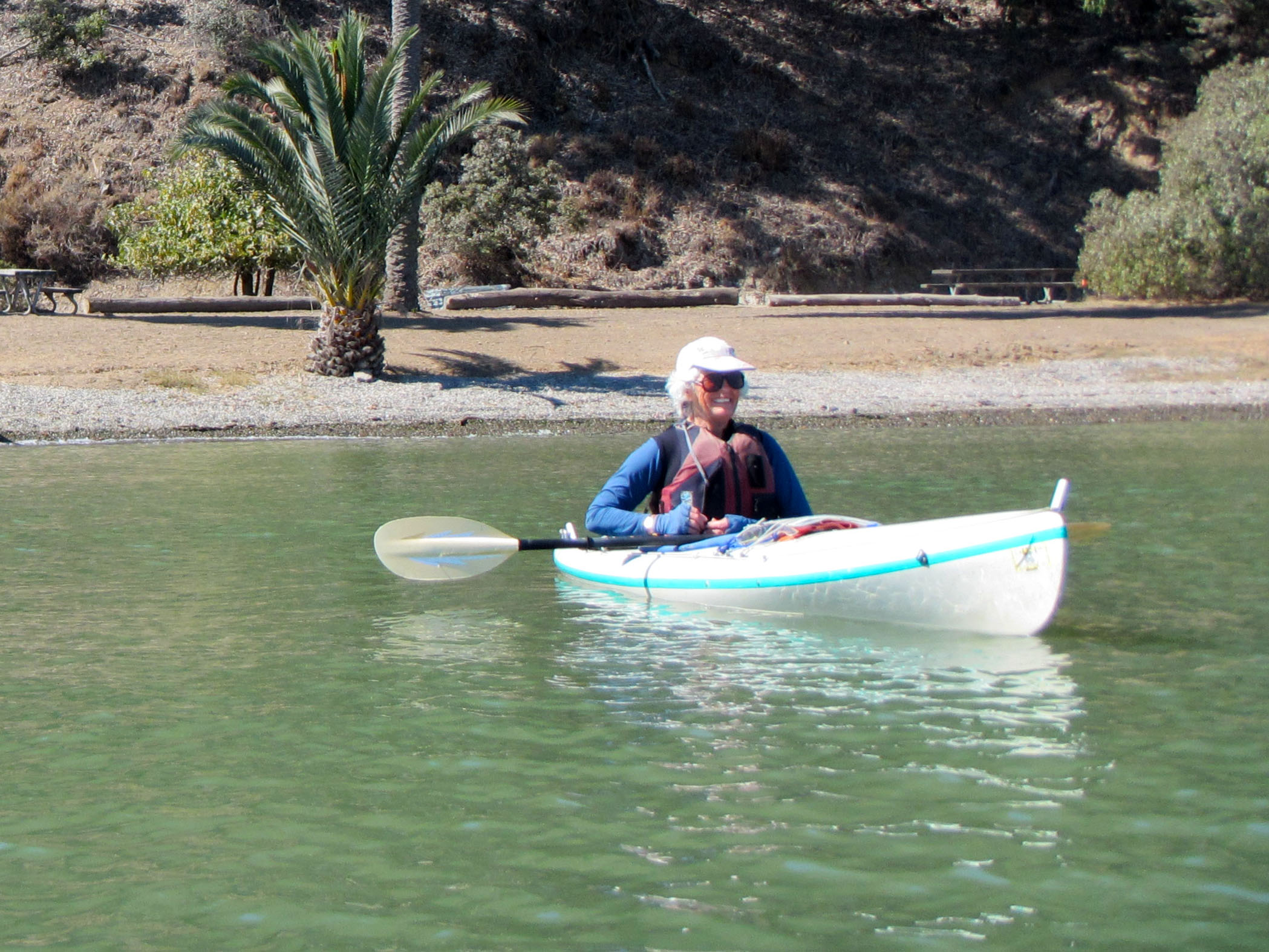 Woman in sunglasses smiling from single kayak, just off the beach