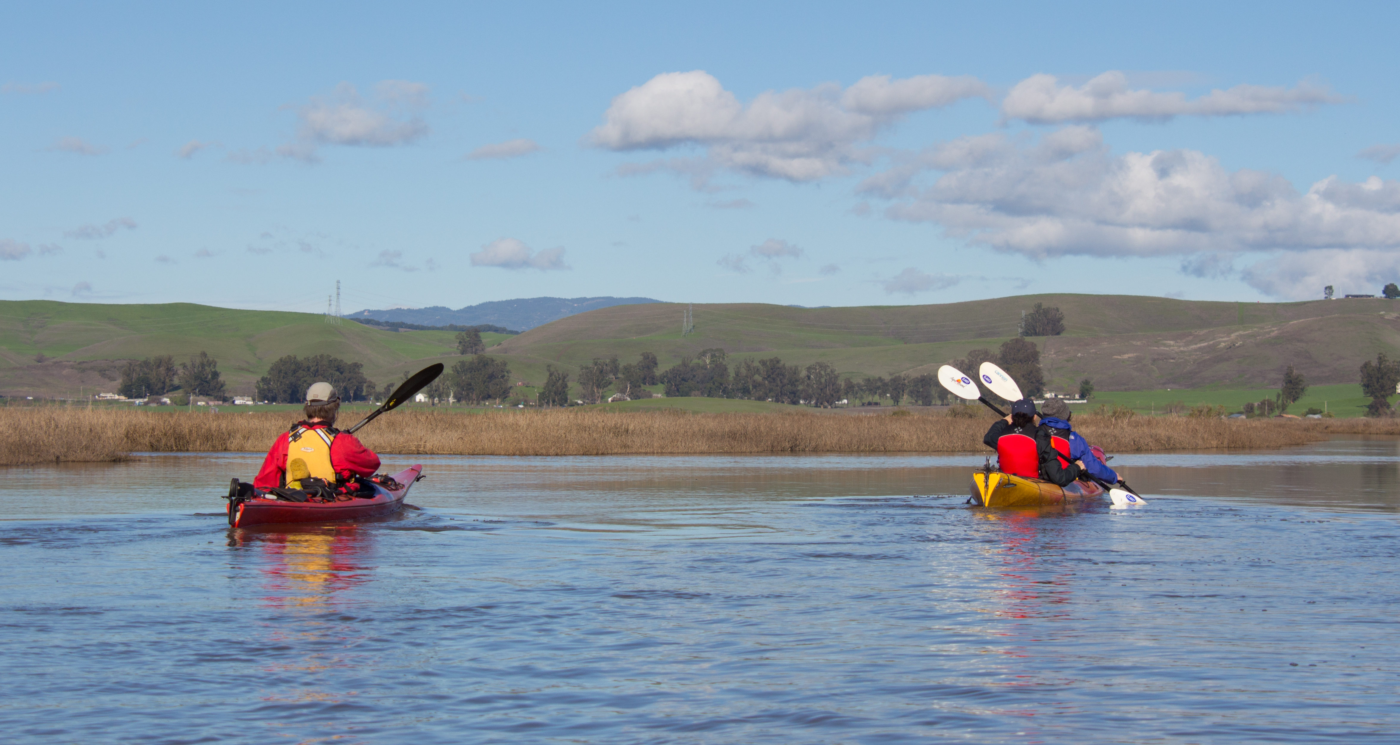 two kayakers paddling away from camera, toward marsh and green hills in distance