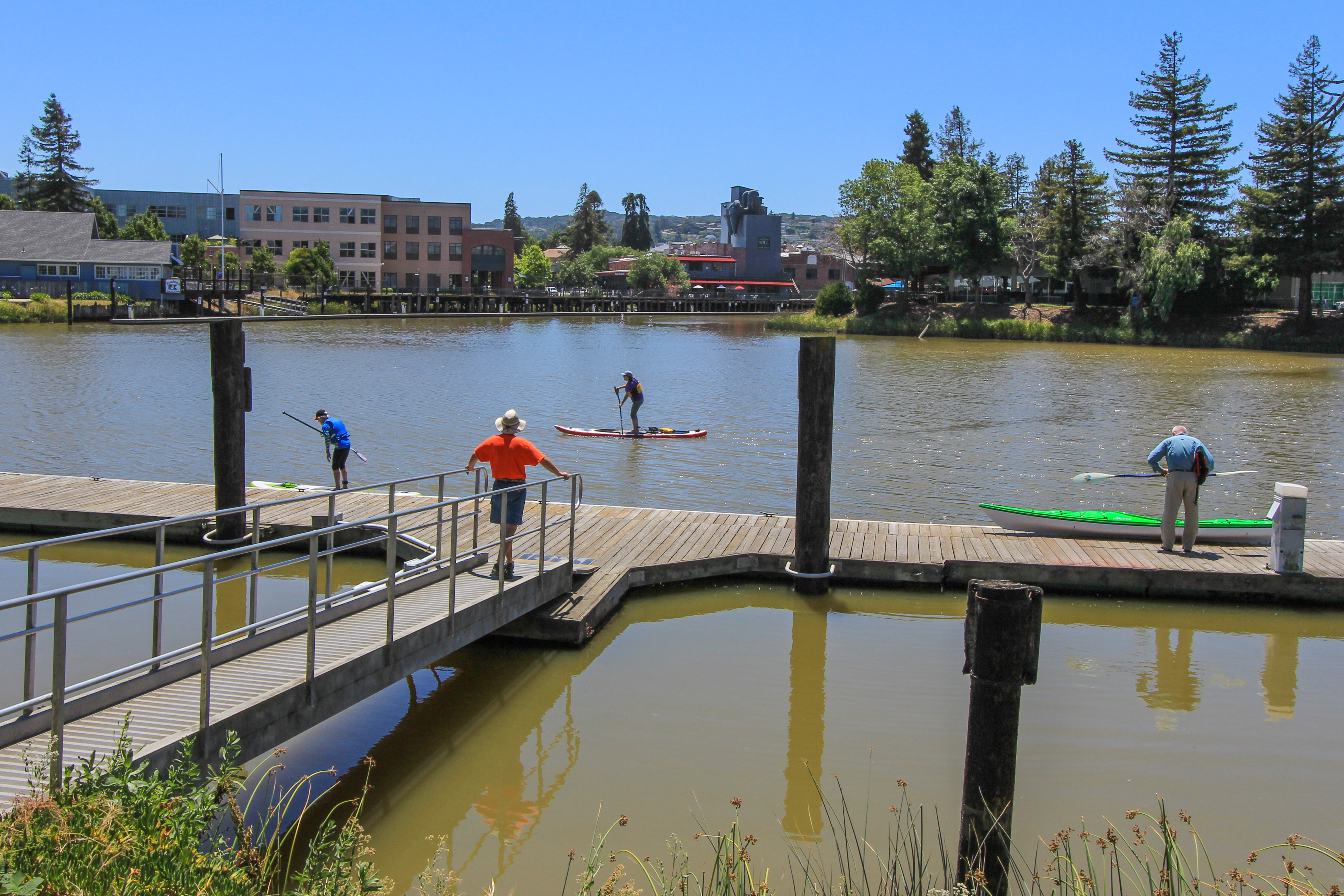 Person on ramp to dock, another on dock getting into kayak, as a standup paddler passes by in the river