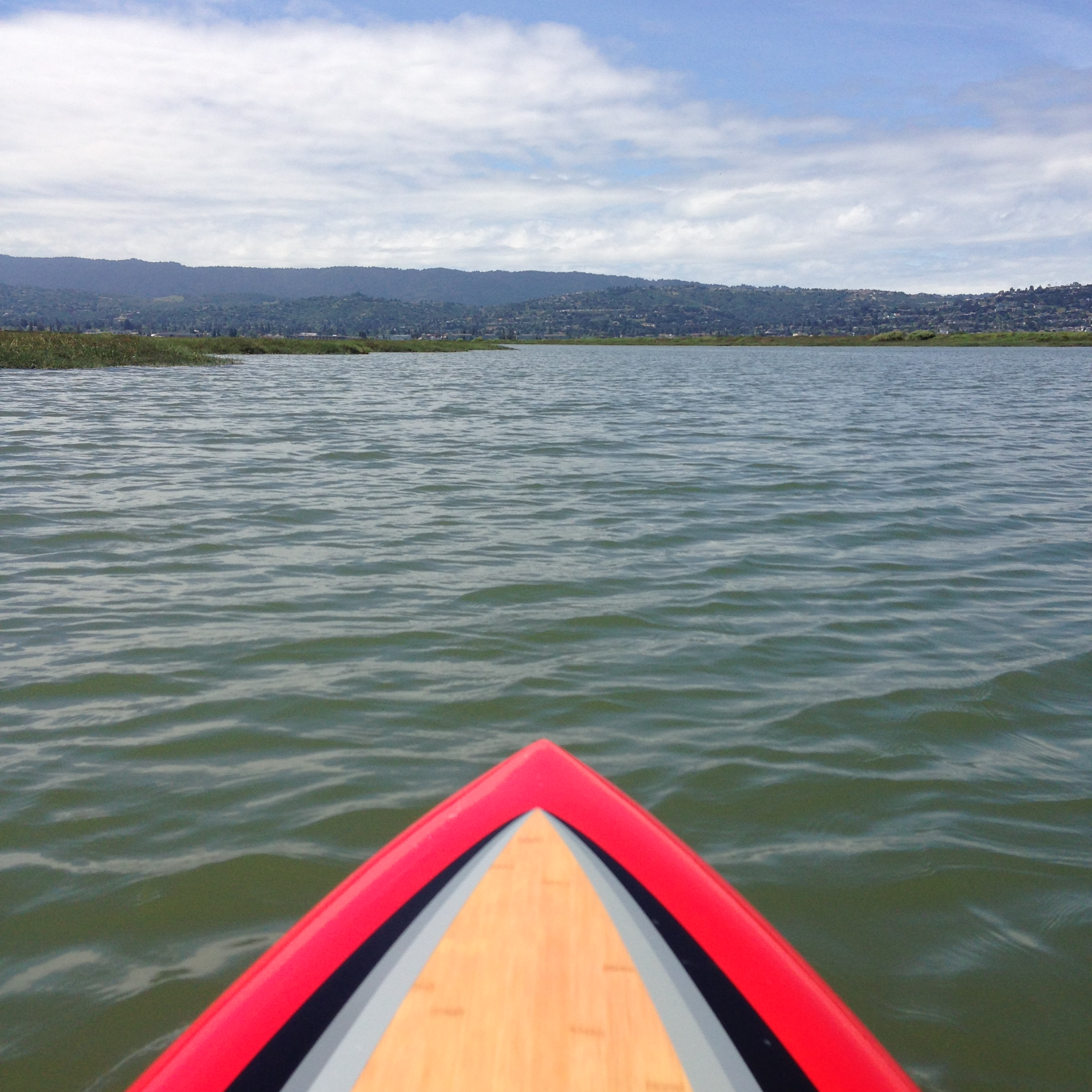Paddleboard-level view of open water and hills beyond
