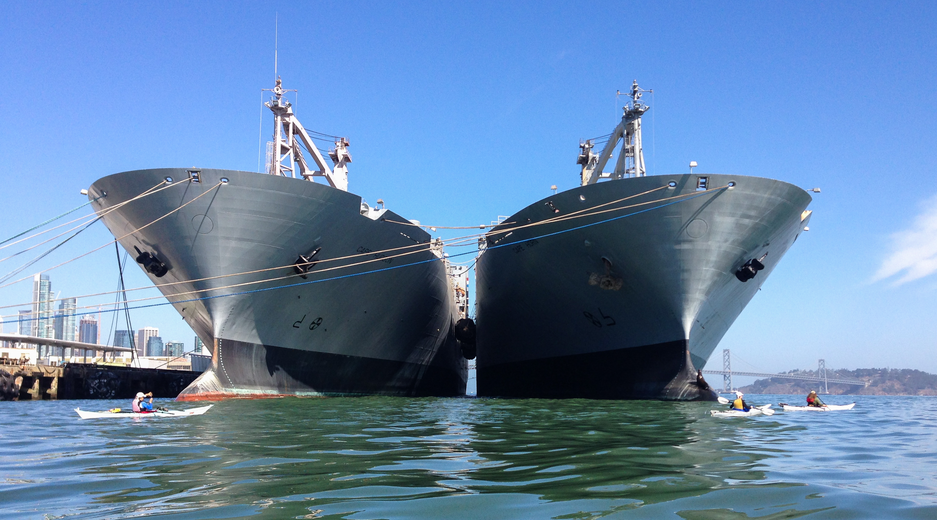 Two large ships loom over kayakers just under their bows