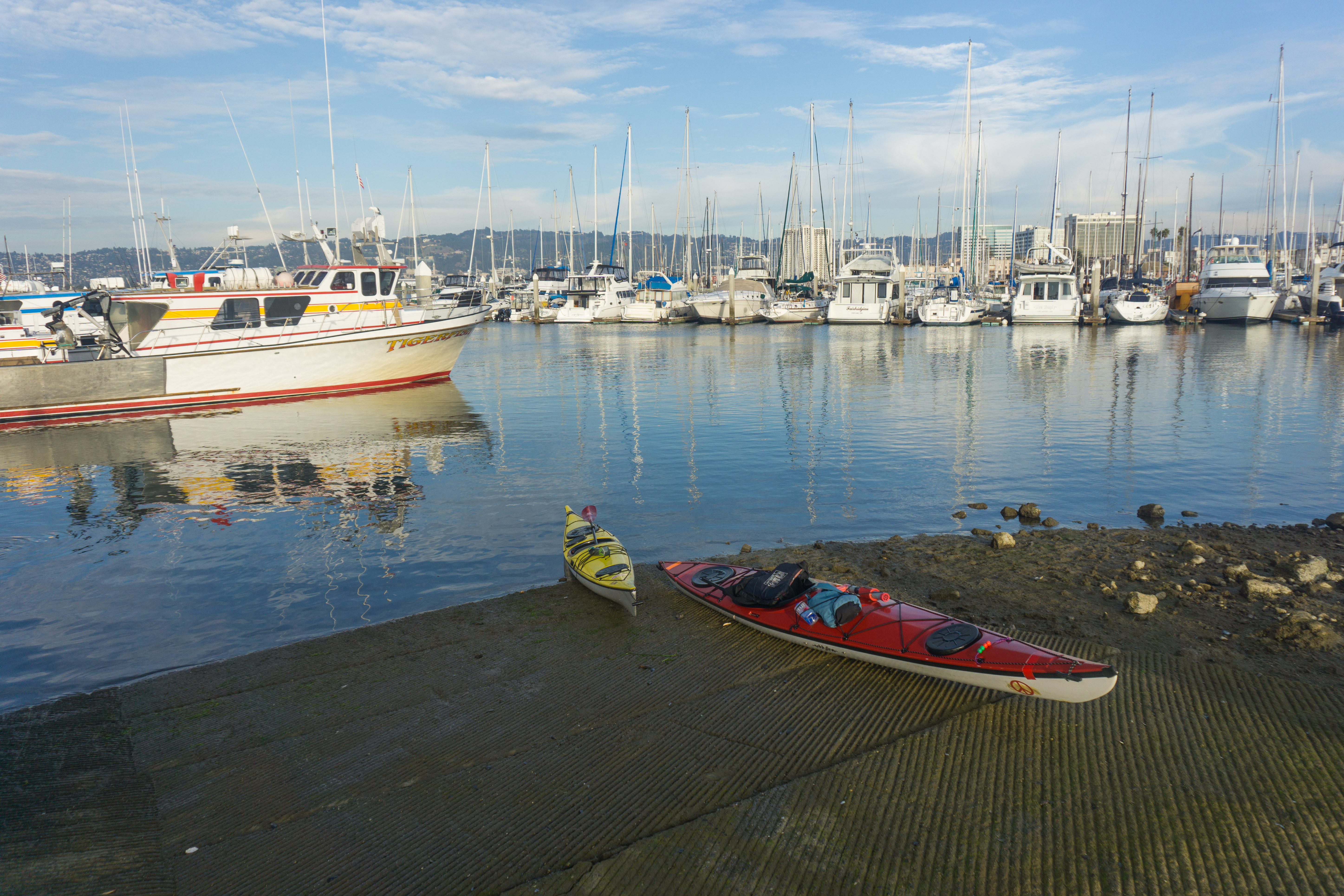 yellow and red kayaks sitting on concrete boat ramp, with many sailboats moored in the marina just offshore
