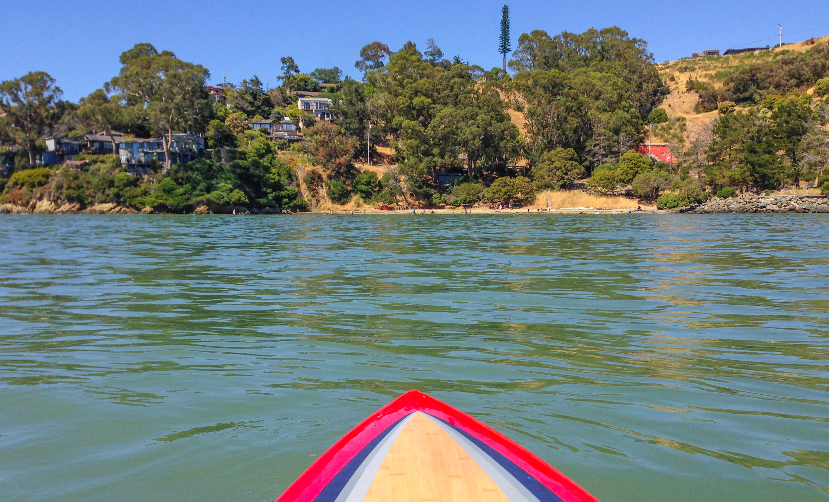 View from kayak with tip in foreground, water and shoreline beyond