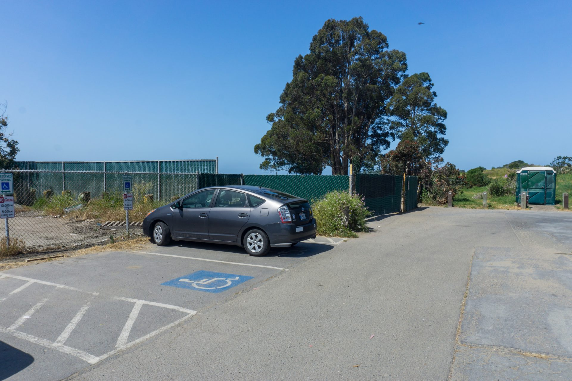 Handicap parking spot, gray Prius. Accessible toilet in distance