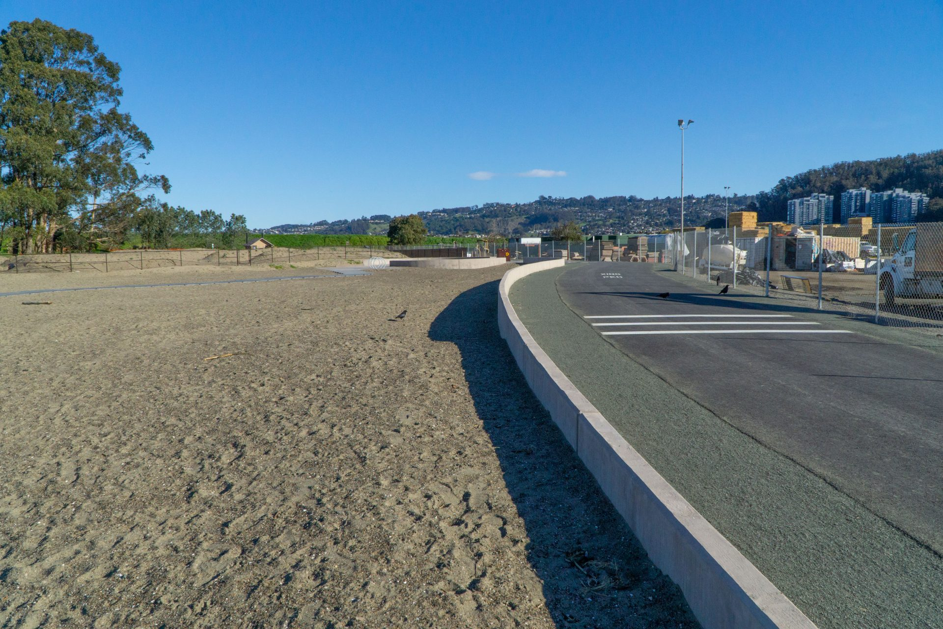 beach on left, short concrete wall, black paved road