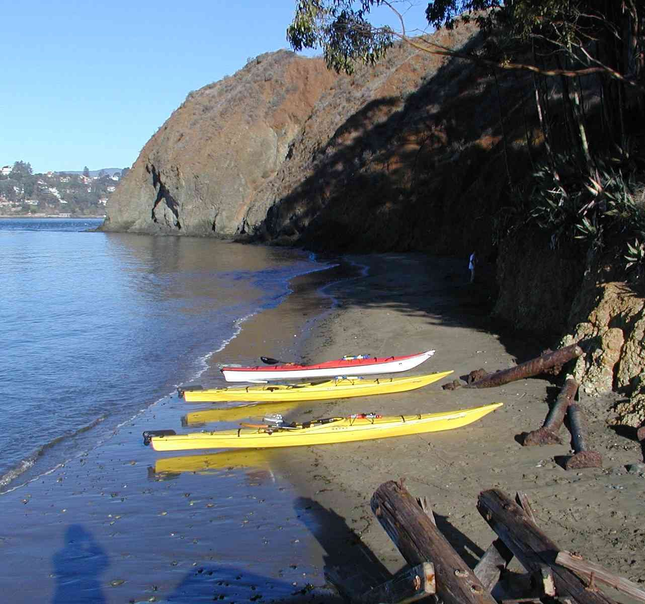 two yellow, one white and orange kayak pulled ashore on narrow beach with tall cliffs and rusty debris