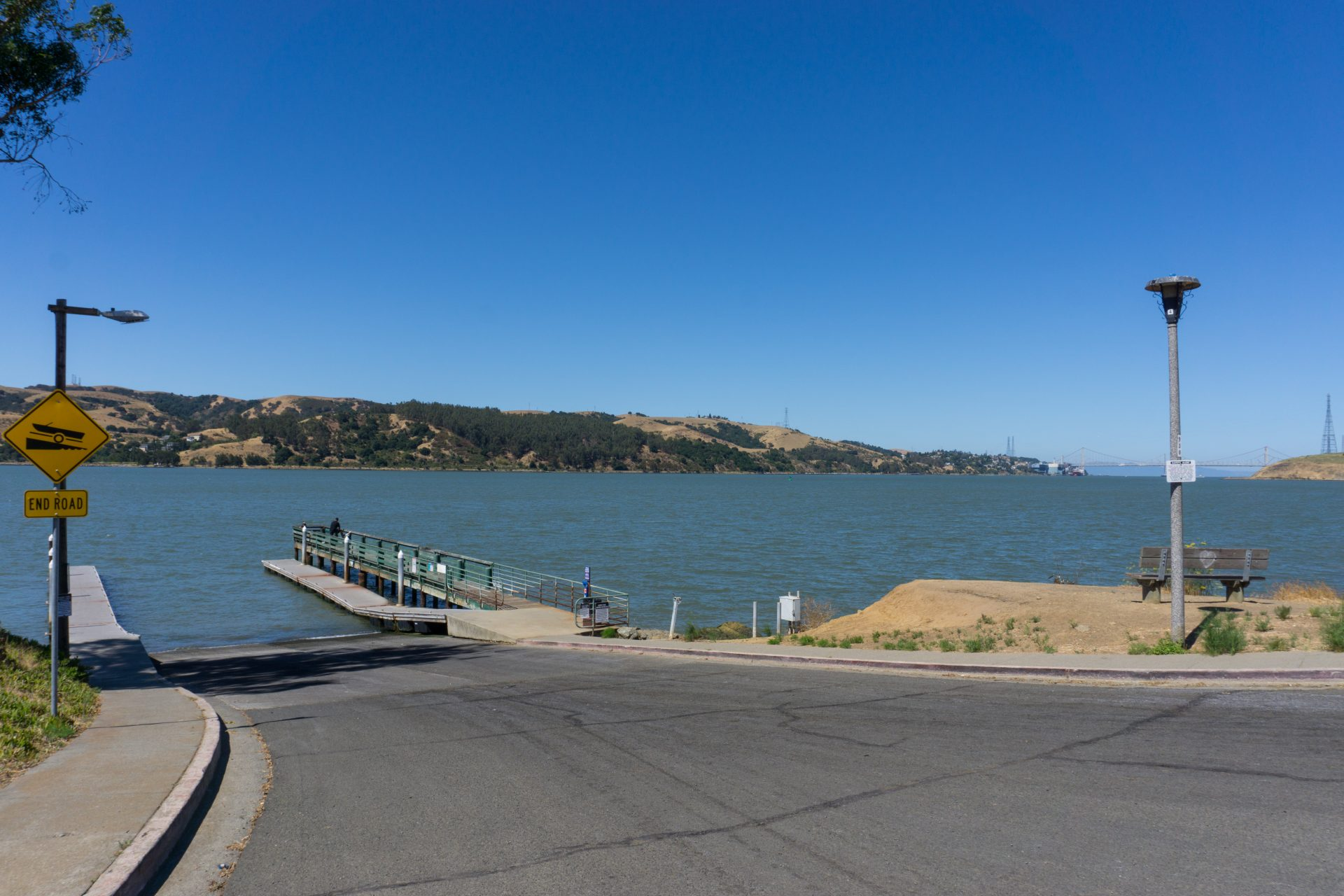 boat ramp descending into water, blue water in middle, green and bbrown hills beyond