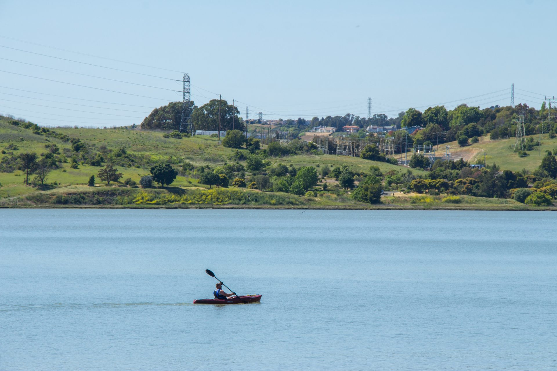 single kayak in foreground, blue water, green hills and powerlines in distance