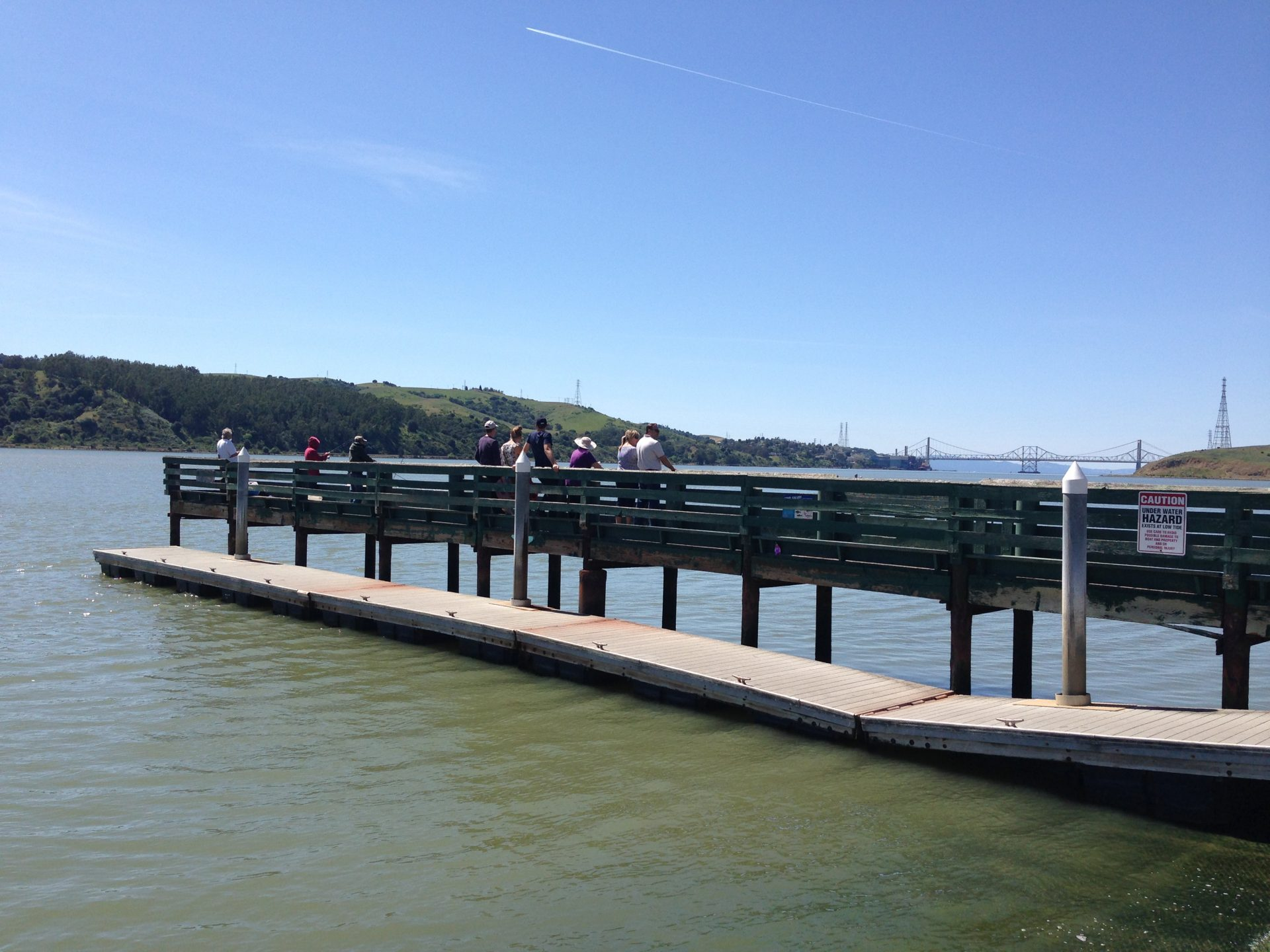 people on fishing pier, floating dock in foreground