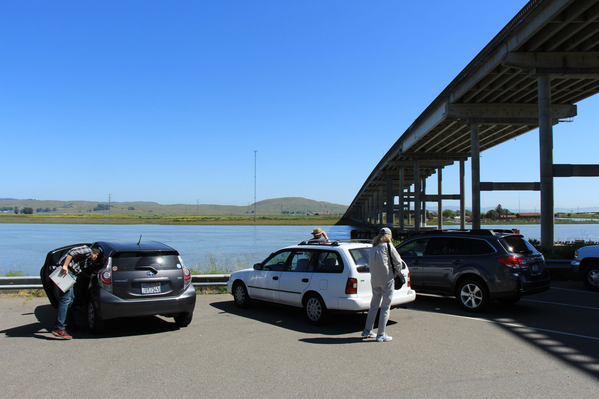 People getting out of cars n parking lot, with viaduct bridge passing overhead