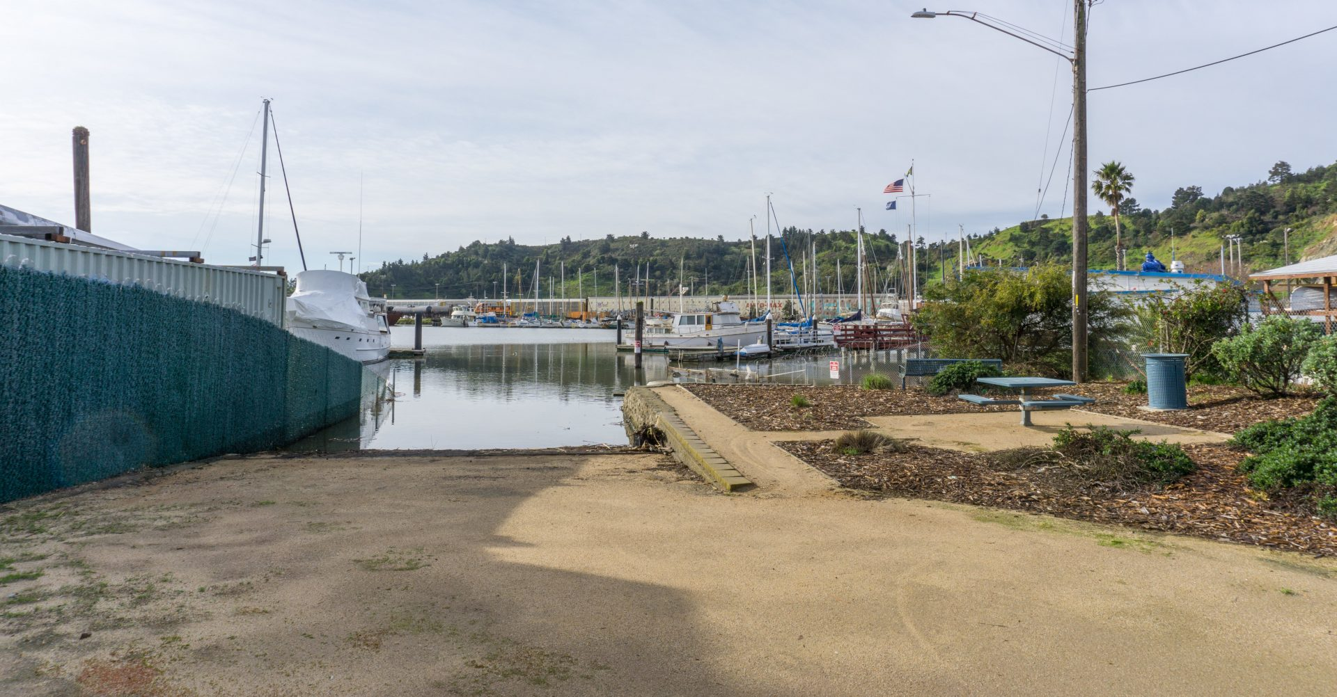 Board ramp descends into water, marina beyond