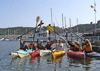 Group of people in colorful kayaks holding their paddles up