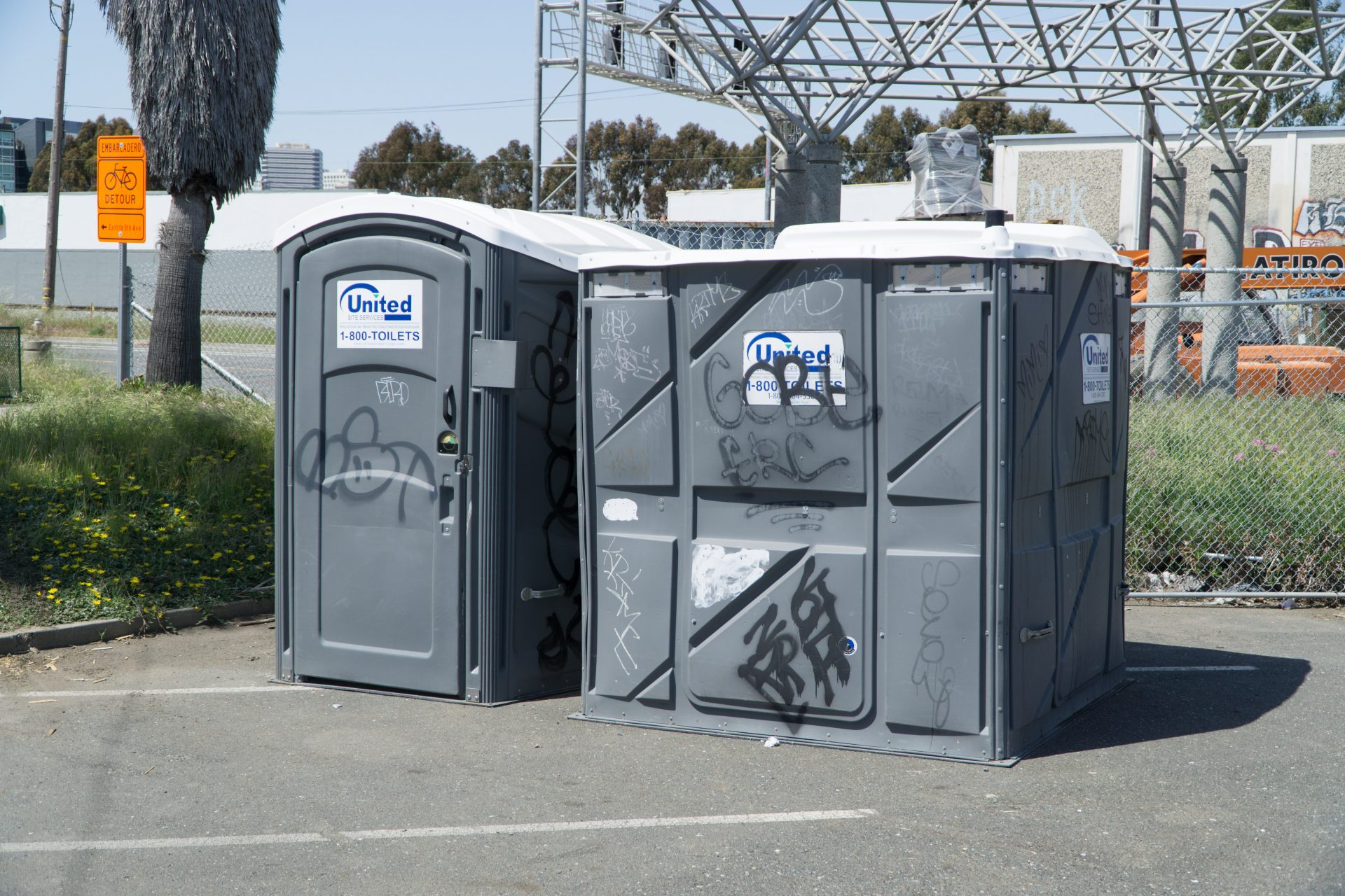 gray portable toilets, one accessible