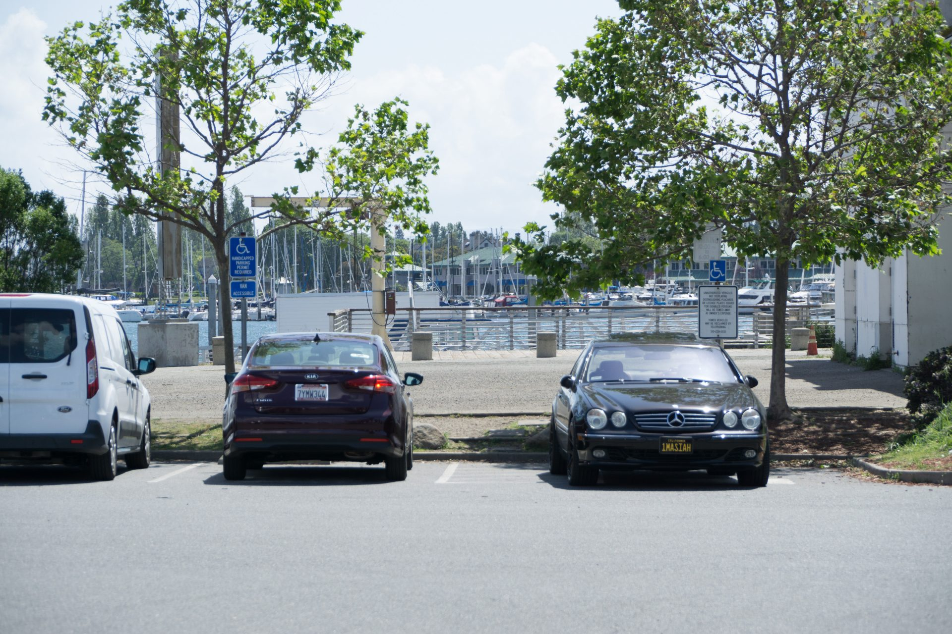 parking lot, two accessible spaces with cars parked