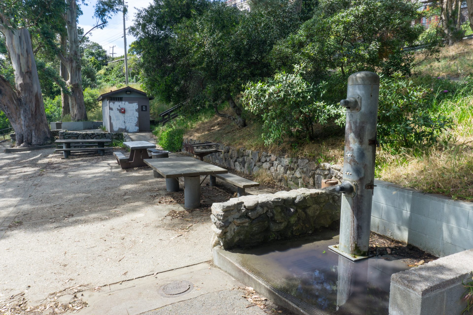 outdoor shower and faucet next to picnic tables