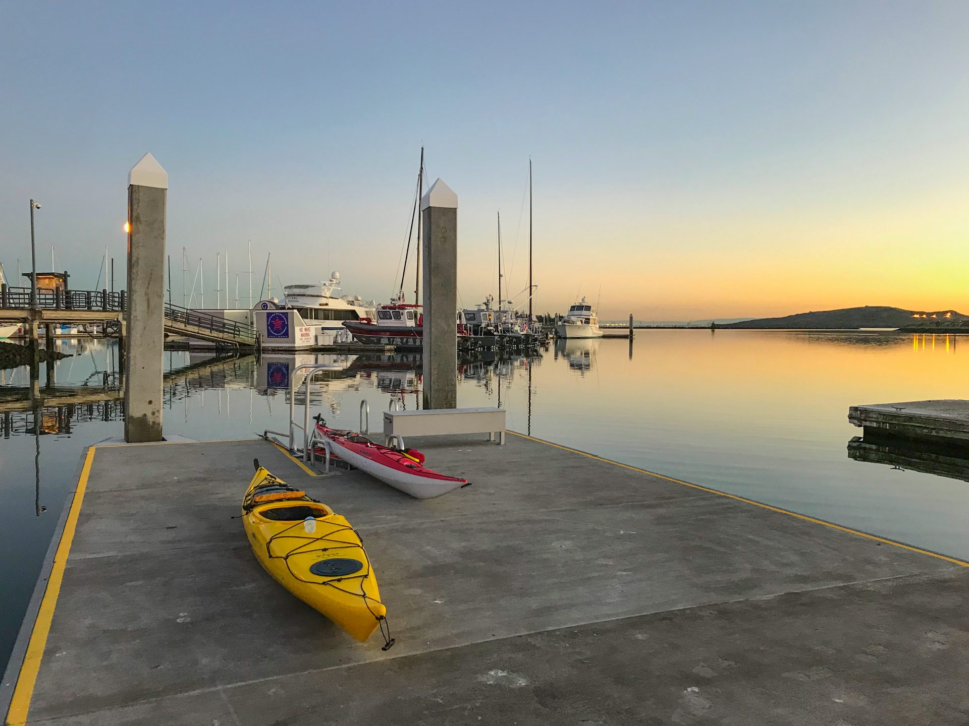 two kayaks on concrete pier, sunset in distance