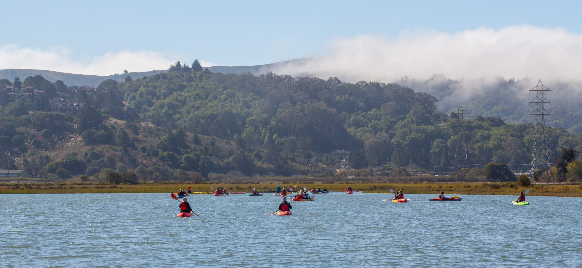 many kayaks on water, marsh and hills with fog in distance