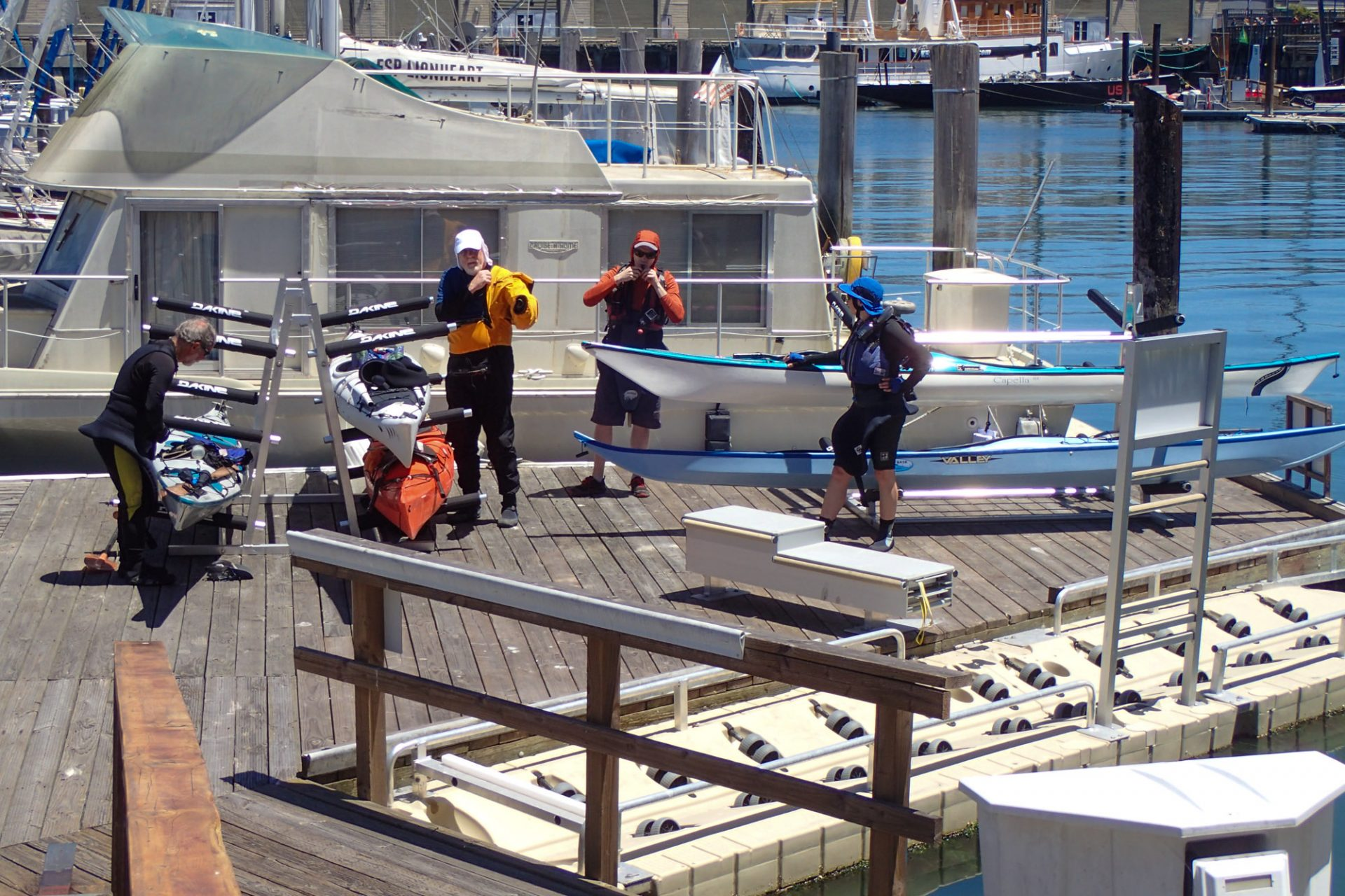 Four people stand among kayaks and racks on wooden pier, putting on jackets