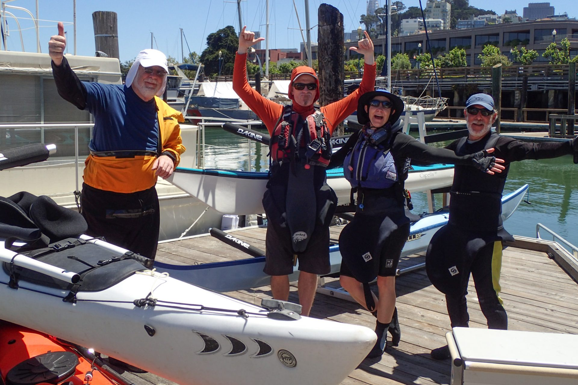 Four people in paddling clothes standing up dock holding their arms out and smiling, surrounded by kayaks