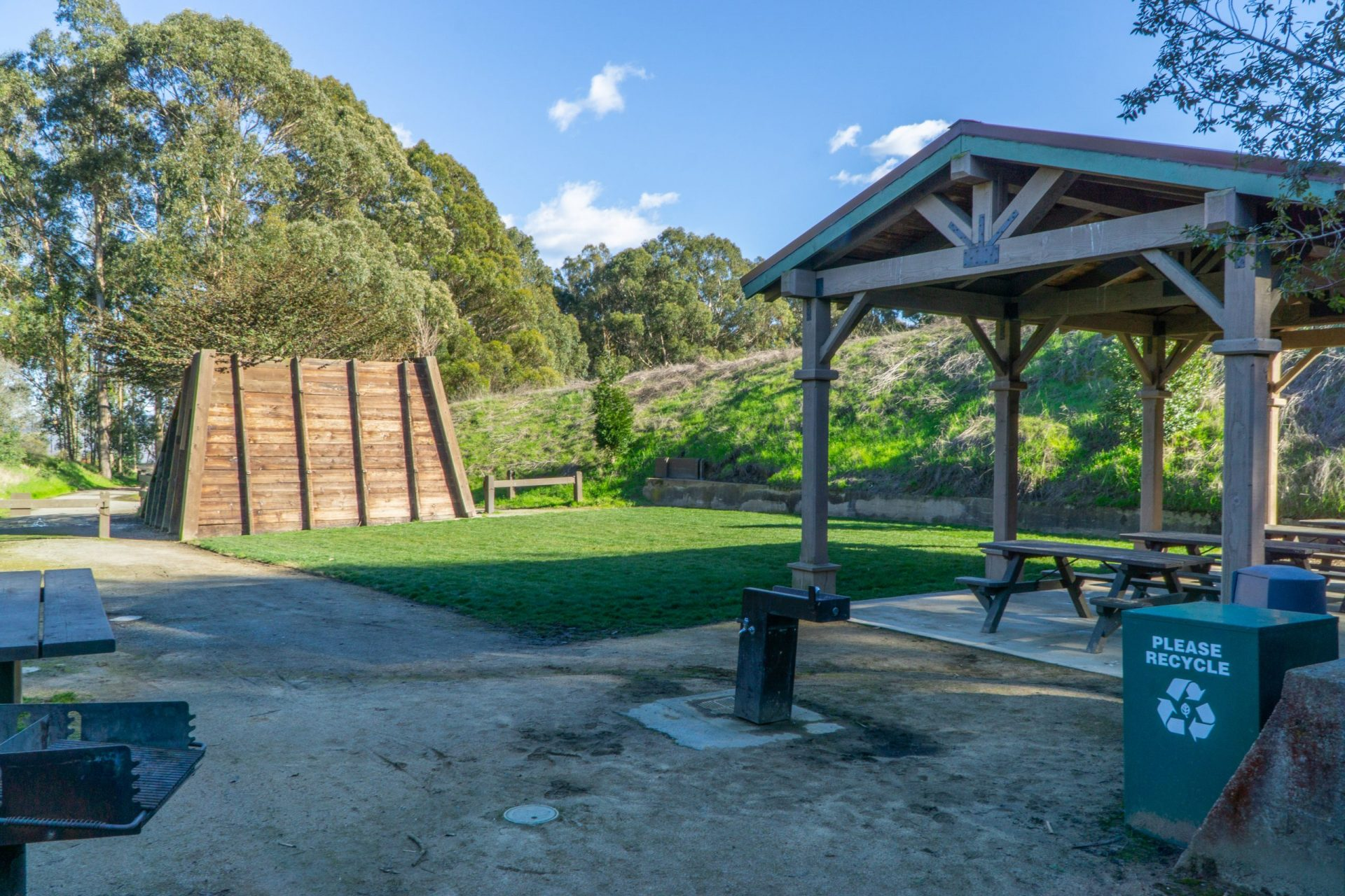 Campground with covered picnic tables, water fountain, and trashcan