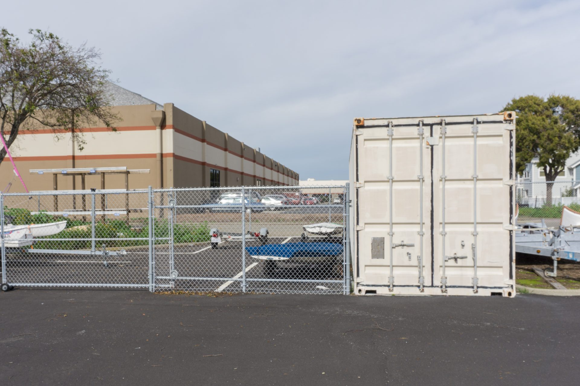 chainlink fence with boats and kayak racks inside, next to a locked shipping container