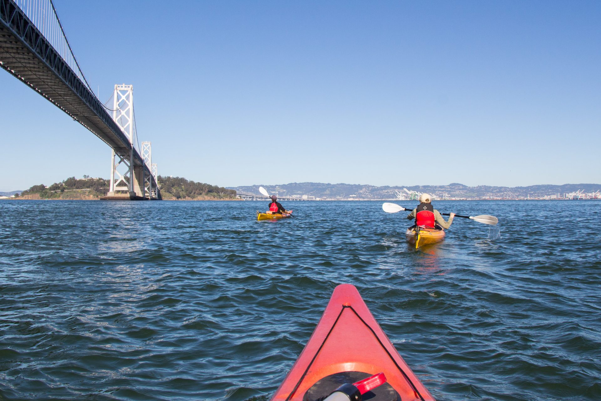 Kayak view of two paddlers, with Bay Bridge on left