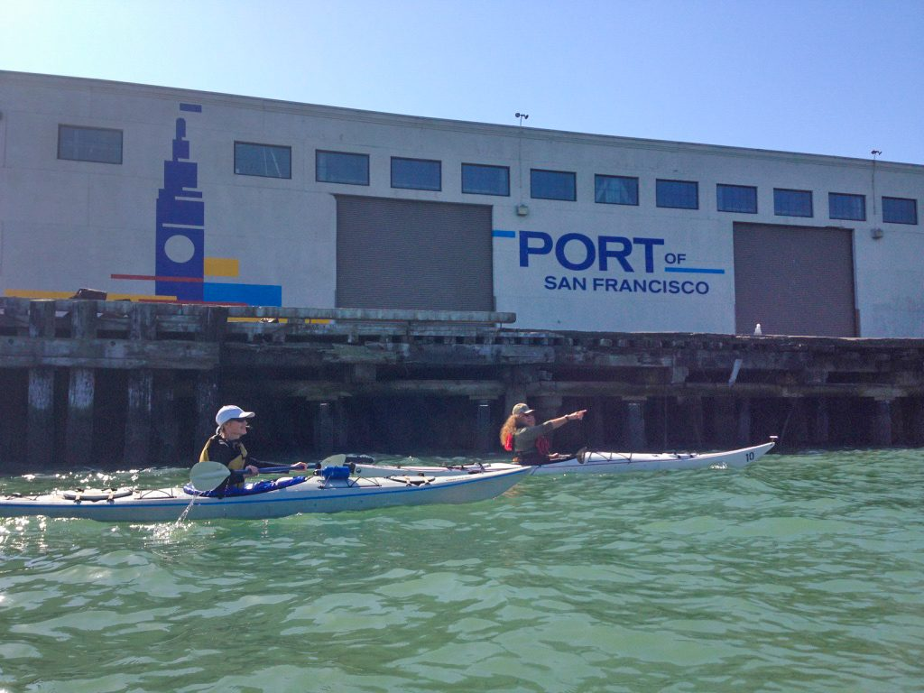Two kayakers, one pointing to right. Behind is a warehouse that says