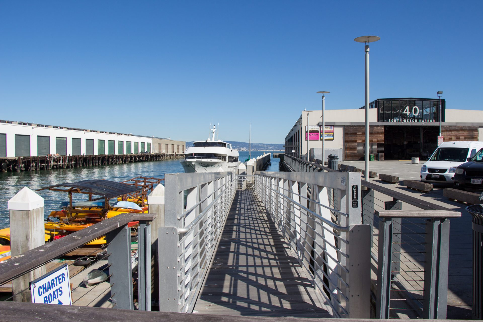 Long narrow walkway with kayaks below on left and large yacht in distance. Pier 40 sign and warehouse on right