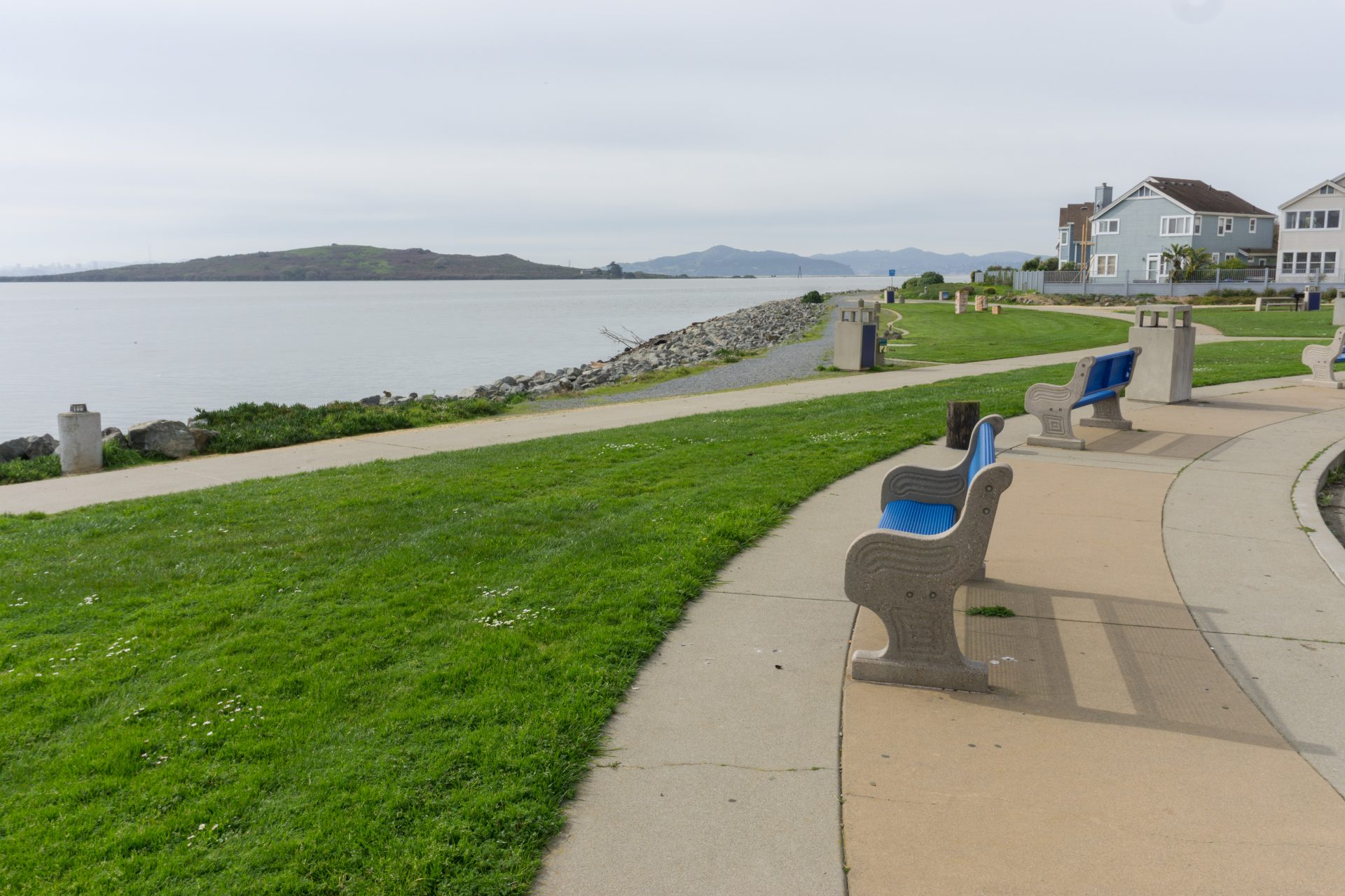 Benches on right, overlooking green grass, paved paths, and the bay