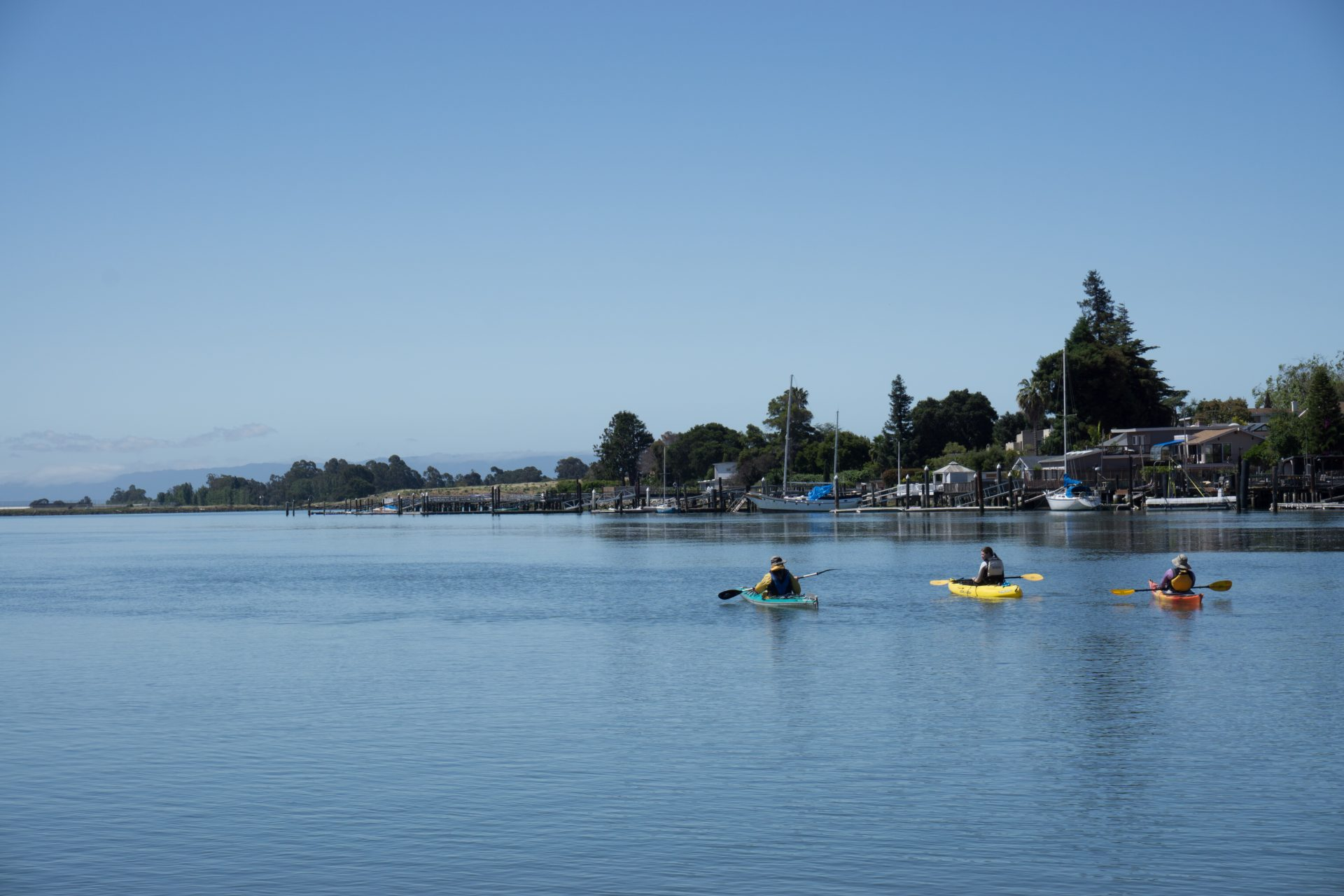 three kayakers in distance on calm waters