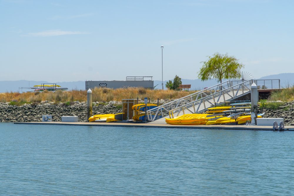 blue water with pier full of yellow kayaks and paddle boards
