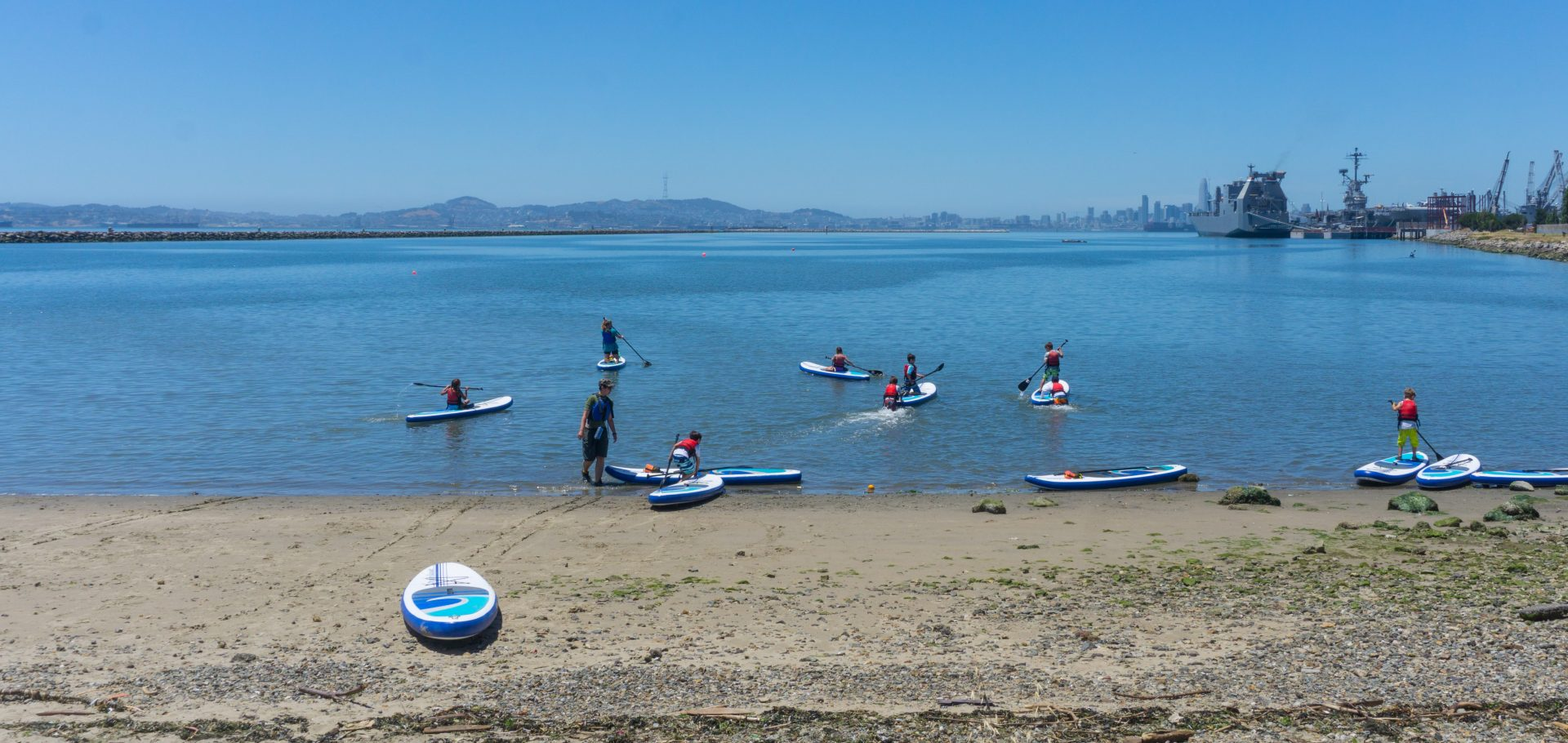 standup paddlers embarking from beach, with one board left behind on beach