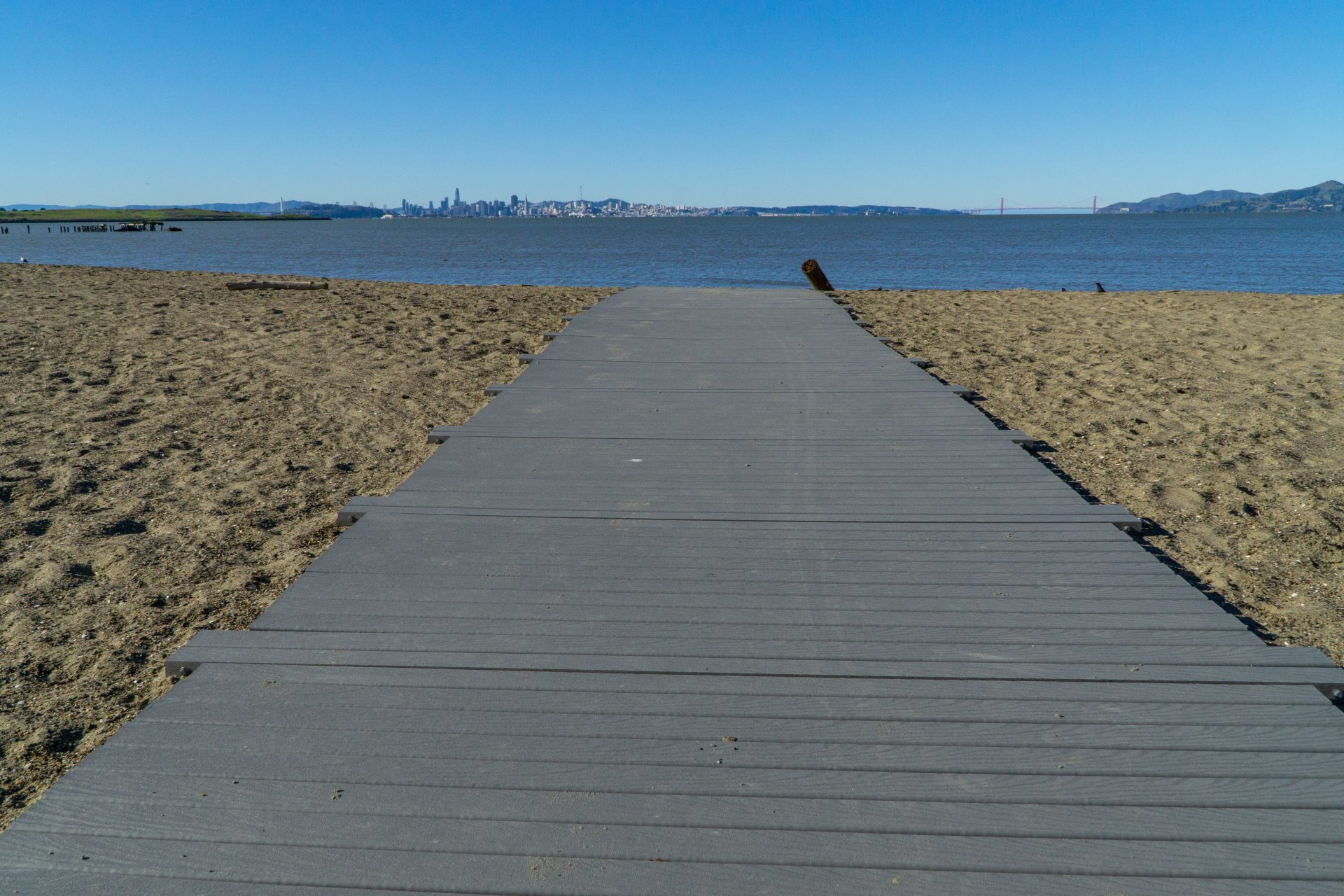 wood gangway running across sand to water