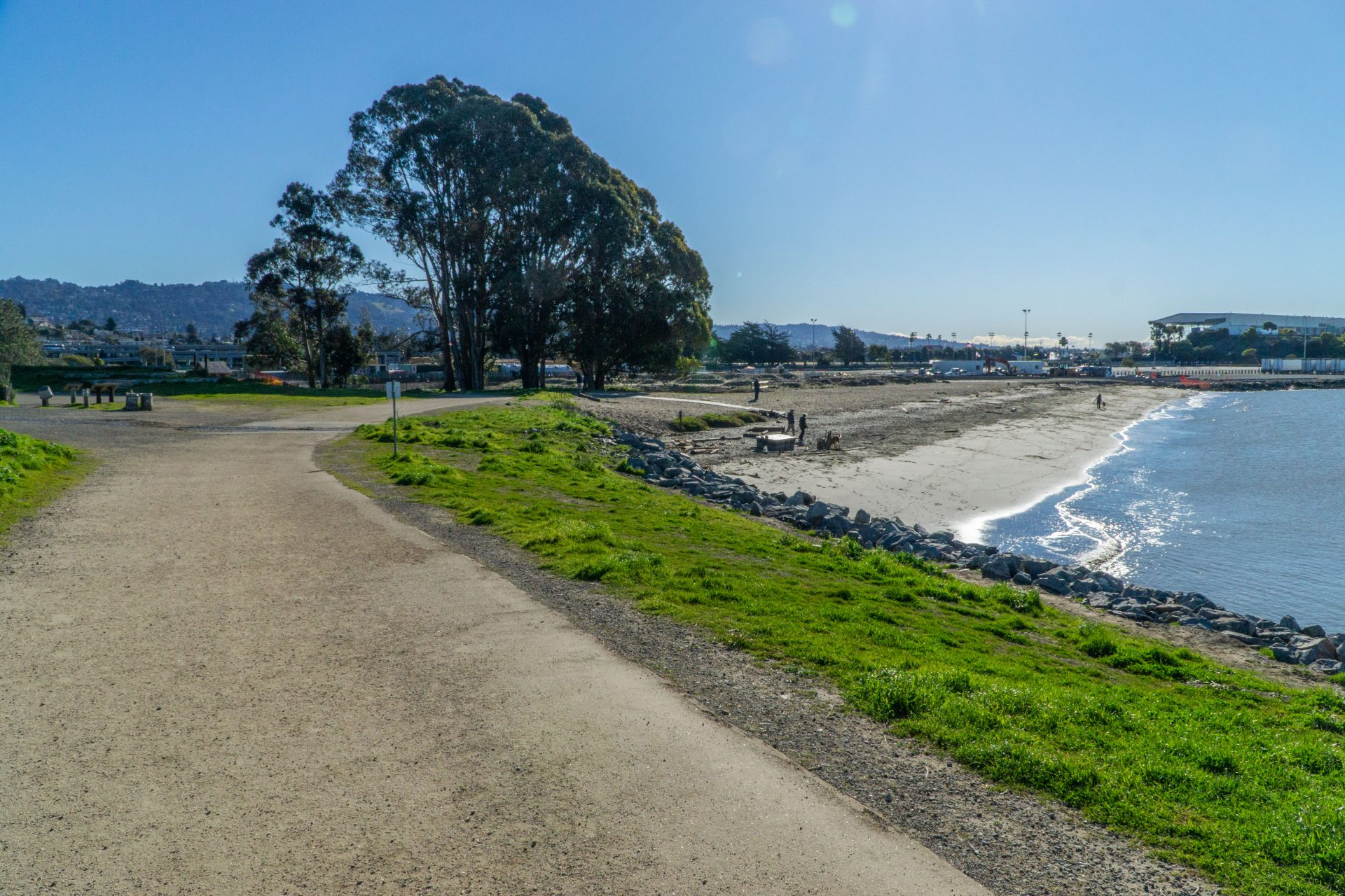 gravel path and green lawn, beach and bay on right