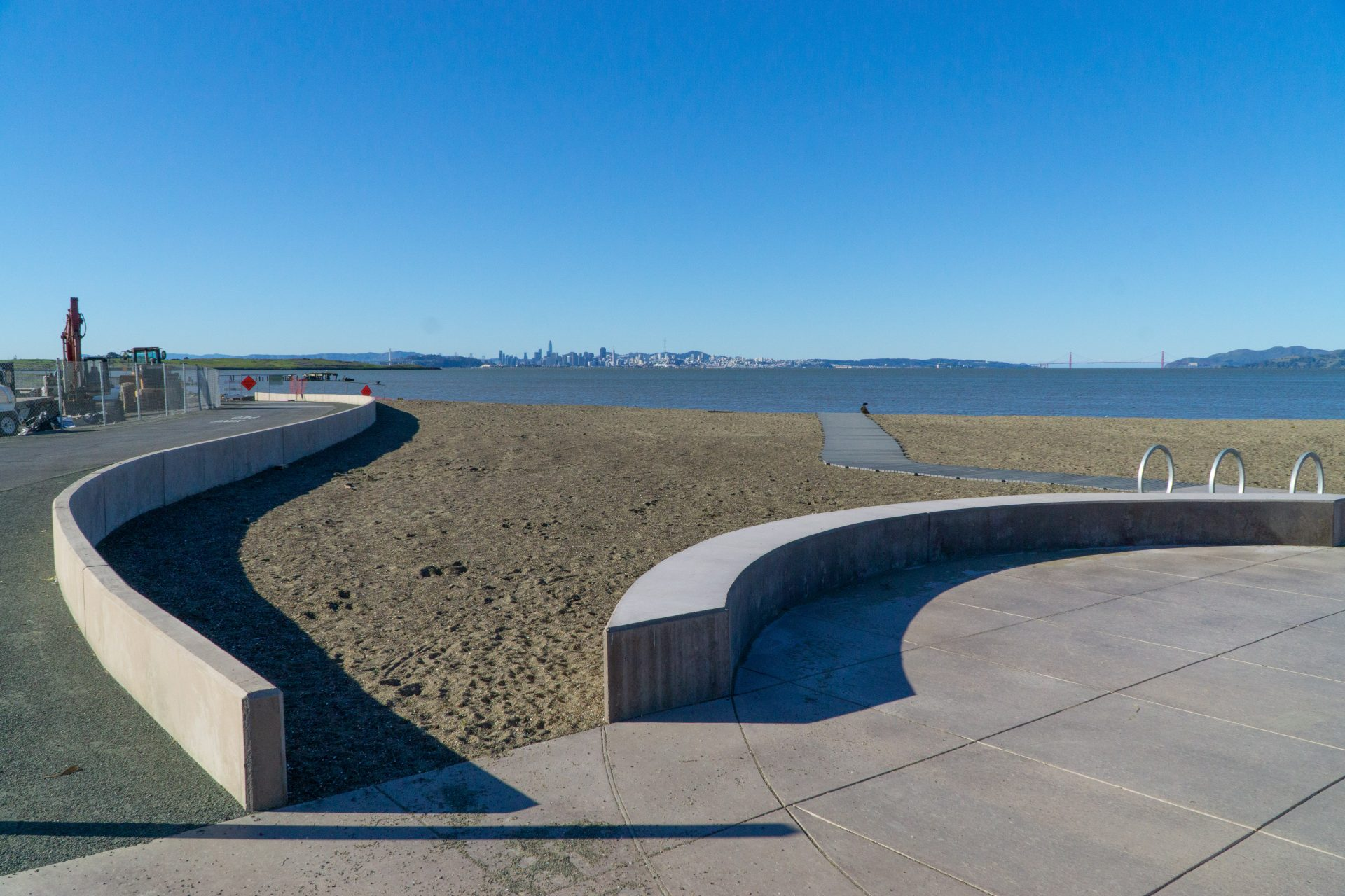 curved concrete walls and path foreground, sandy beach and bay beyond