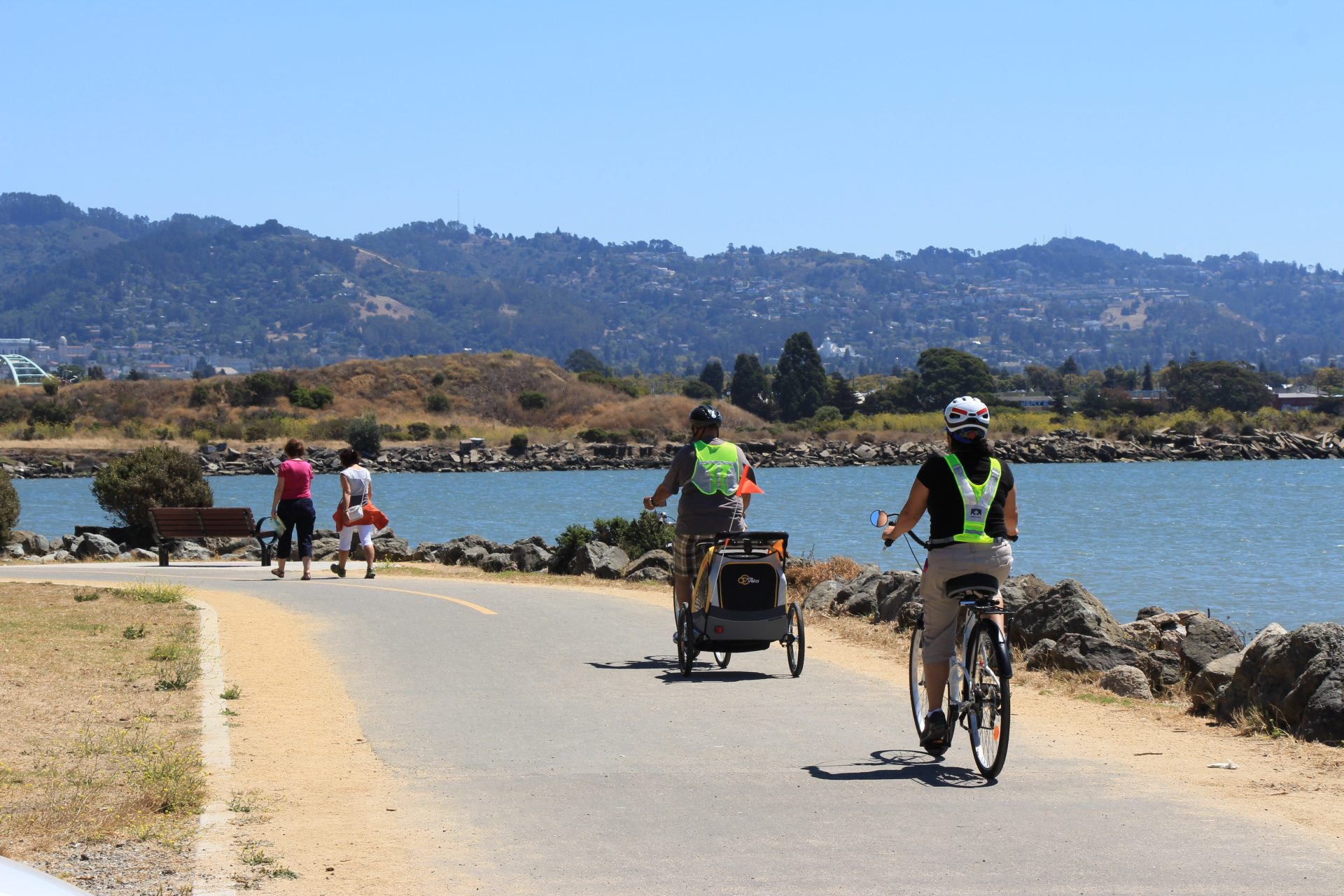 Two bicyclists, one with a child trailer ride on paved path, passing two pedestrians, with bay and hills in distance