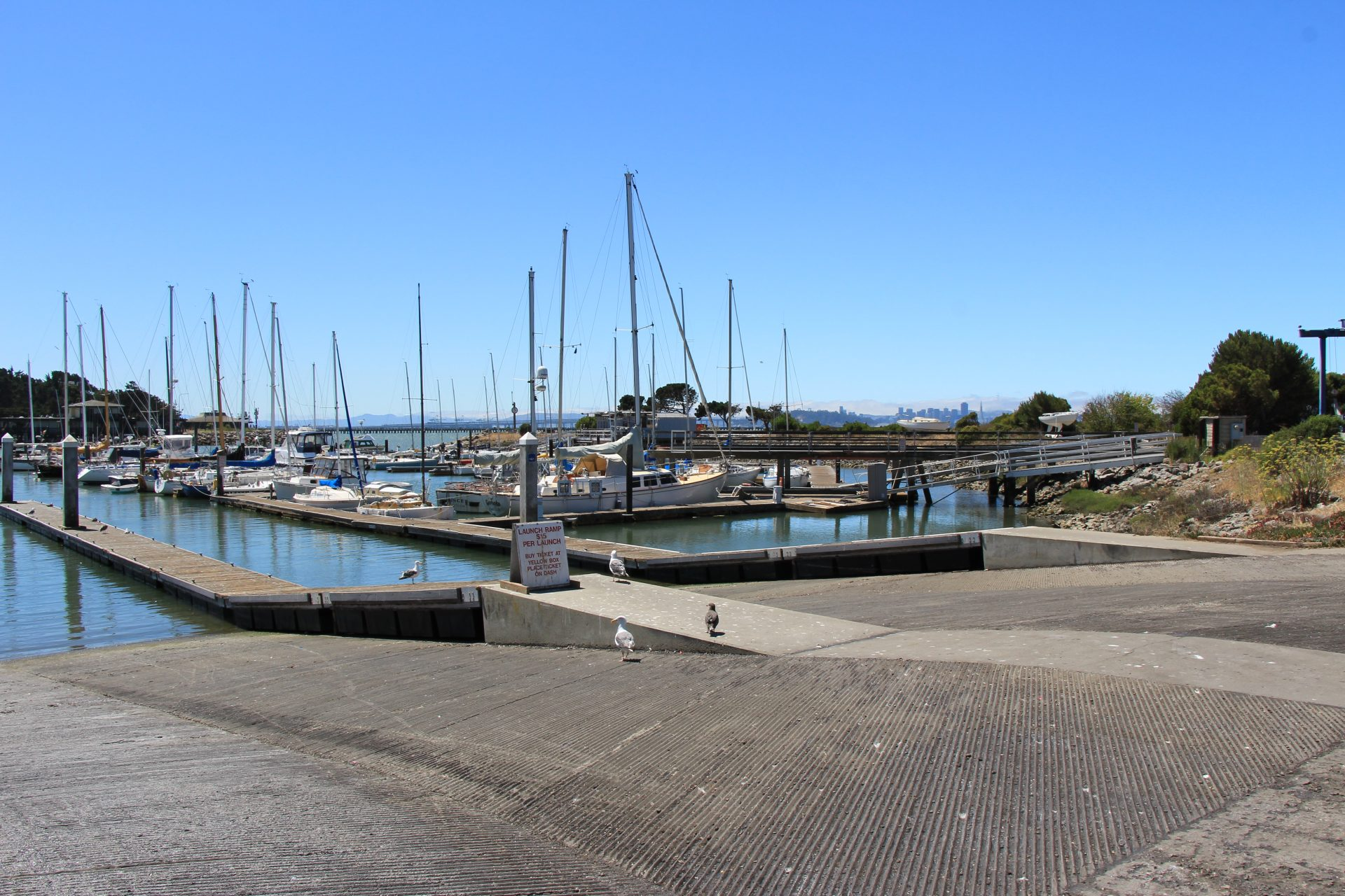 Wide boat ramp descending into water, with sailboats moored beyond