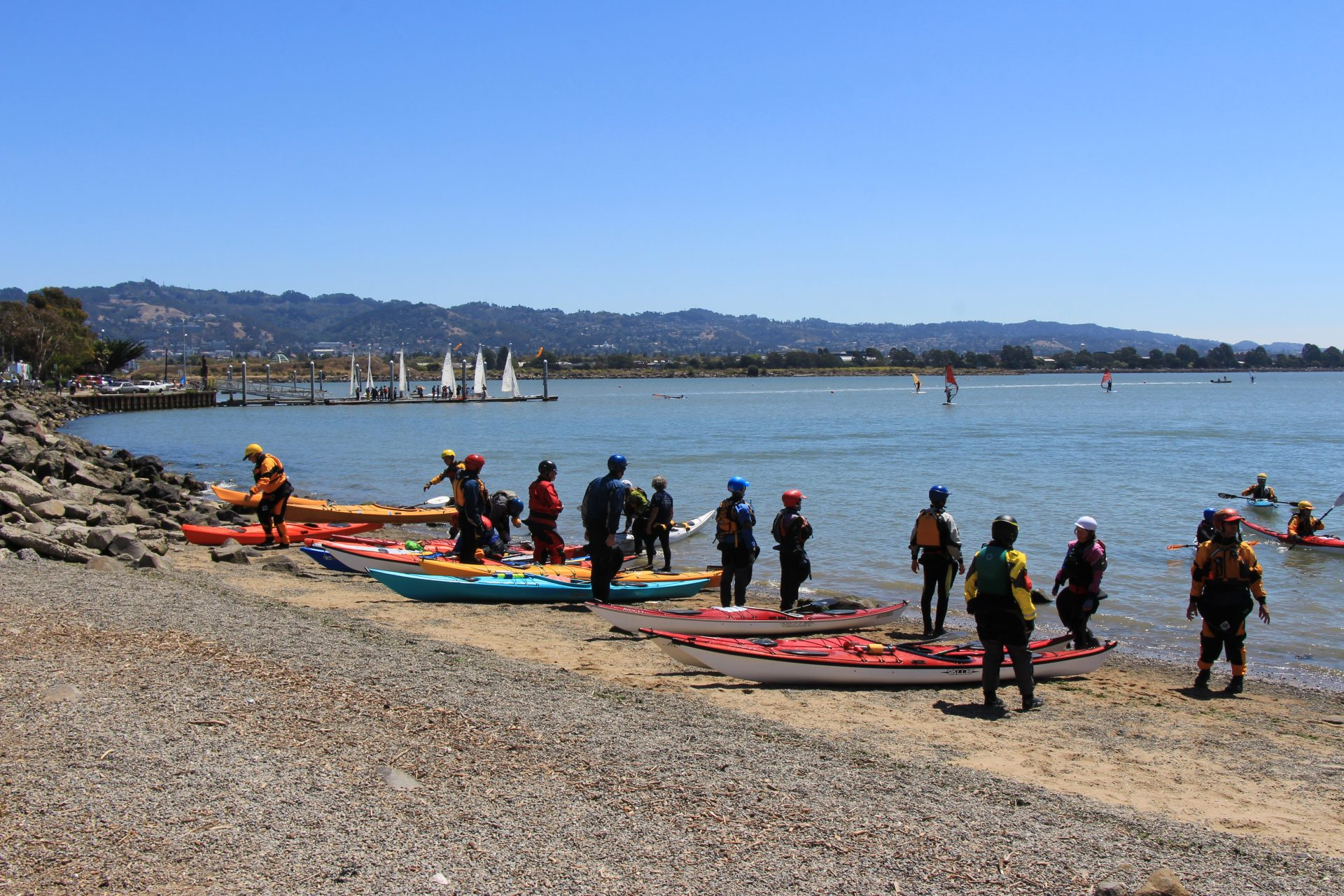 Large group of kayakers milling around boats on sandy beach, with sailboats in distance