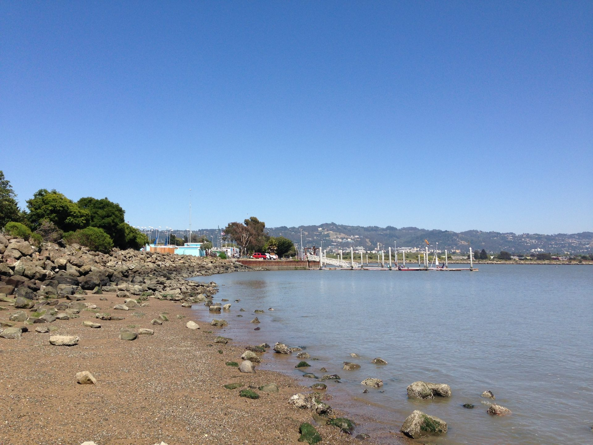 Pebbly beach in foreground, and floating dock in distance along the shore