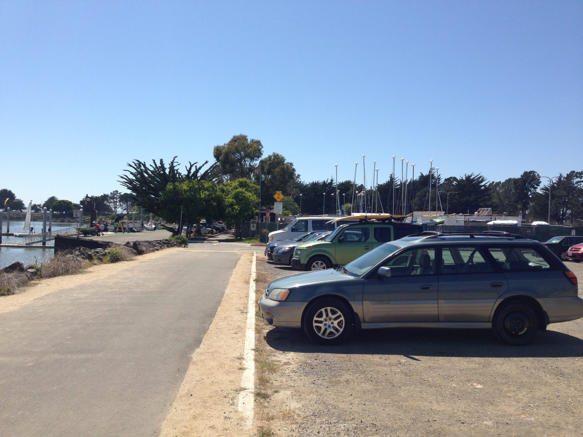 Wide paved path on left, gravel parking lot on right with several cars