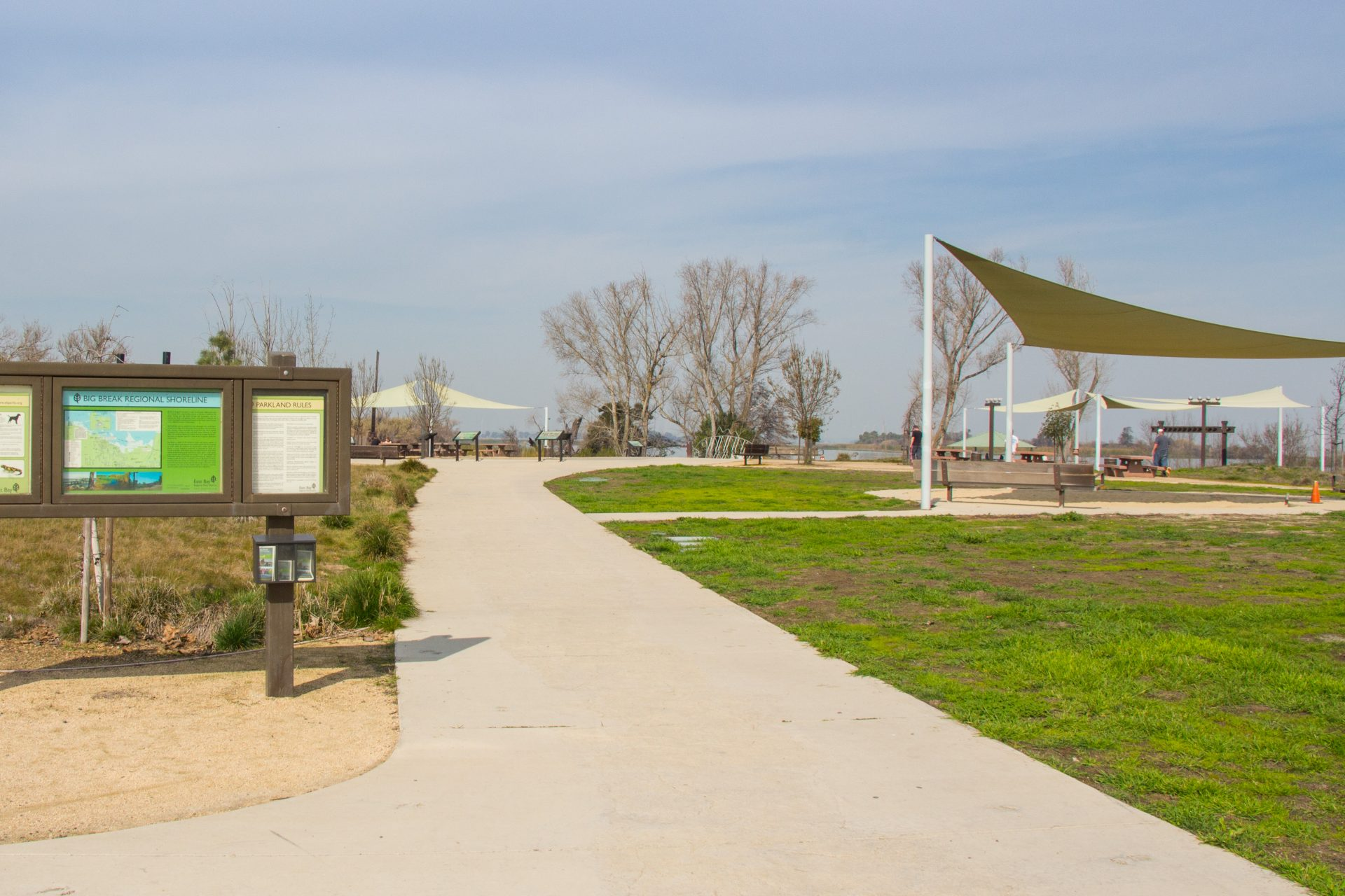 path with sign kiosk on left and shade canopy on right