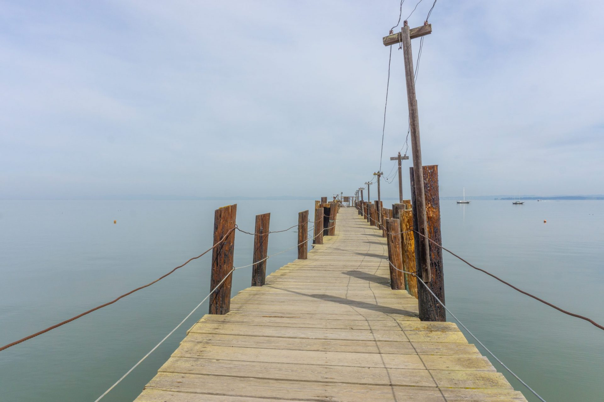 wooden pier with cable railings going straight over water