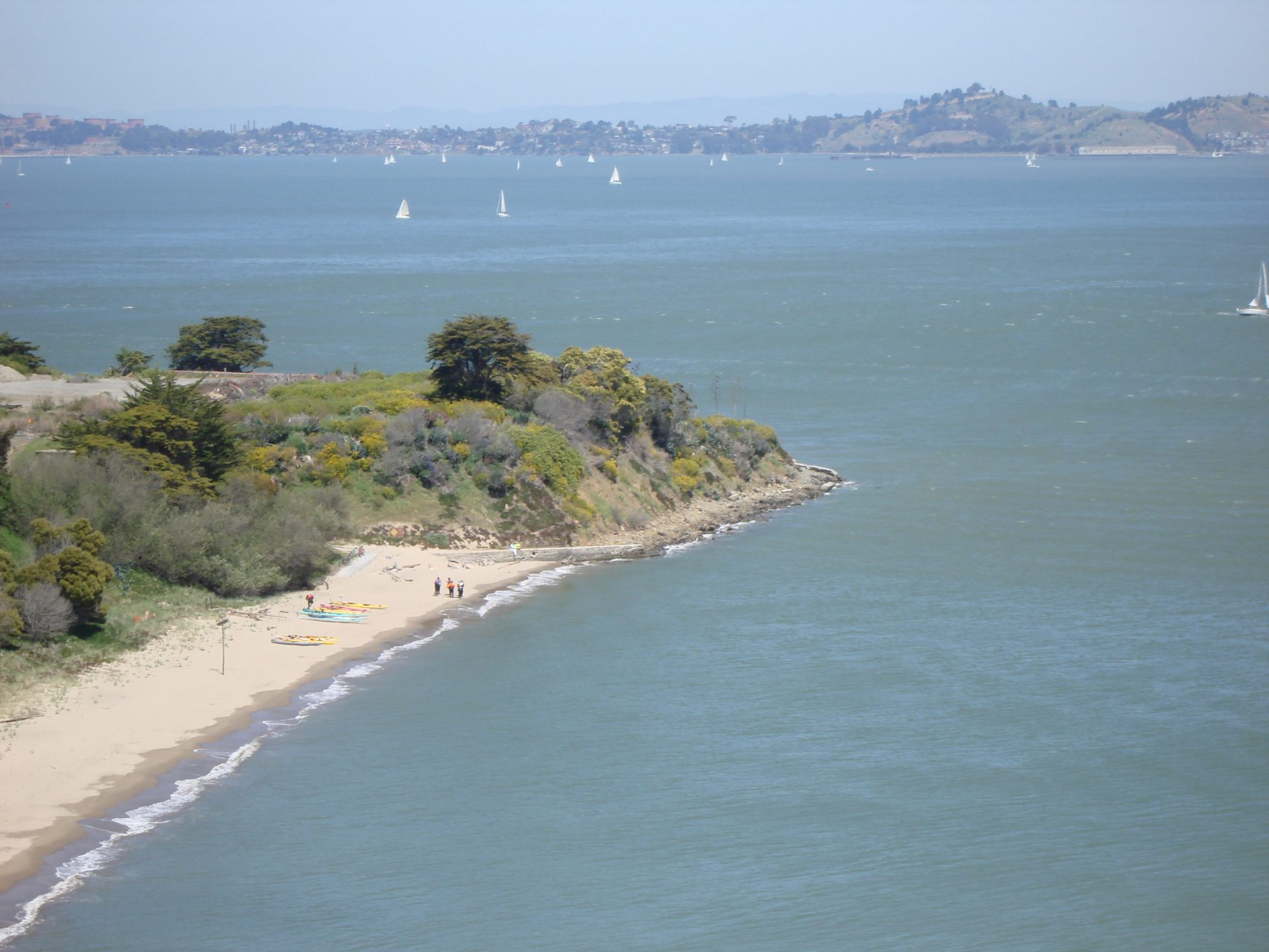 distant view down to beach with kayaks, wooded point, bay beyond
