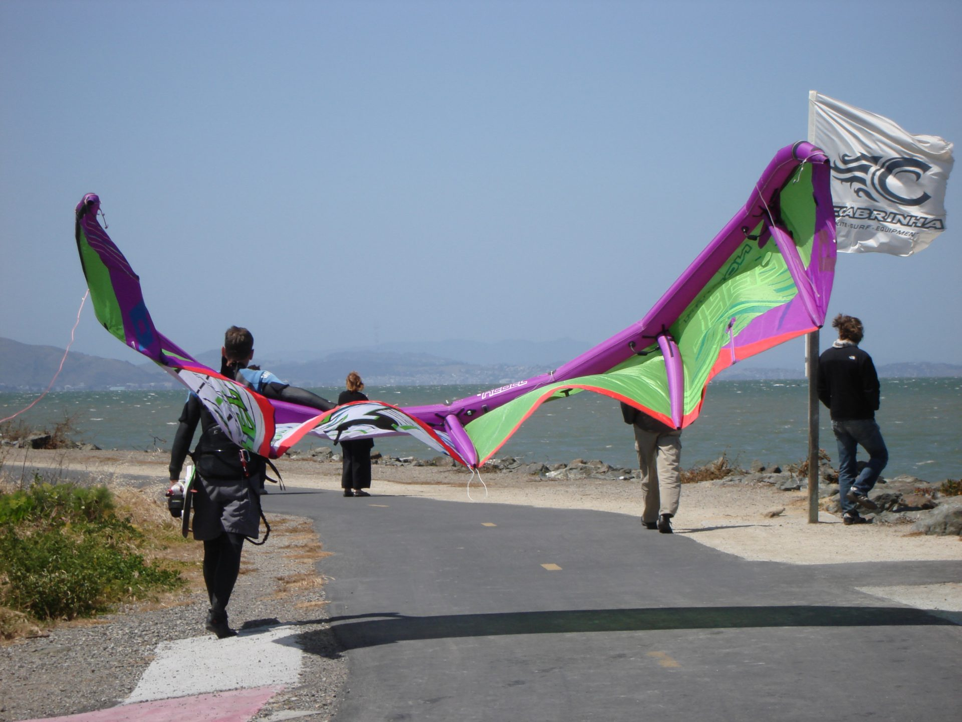 person carrying large, colorful kite for kiteboarding